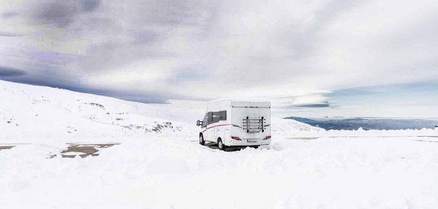 RV in snowfield under dark skies