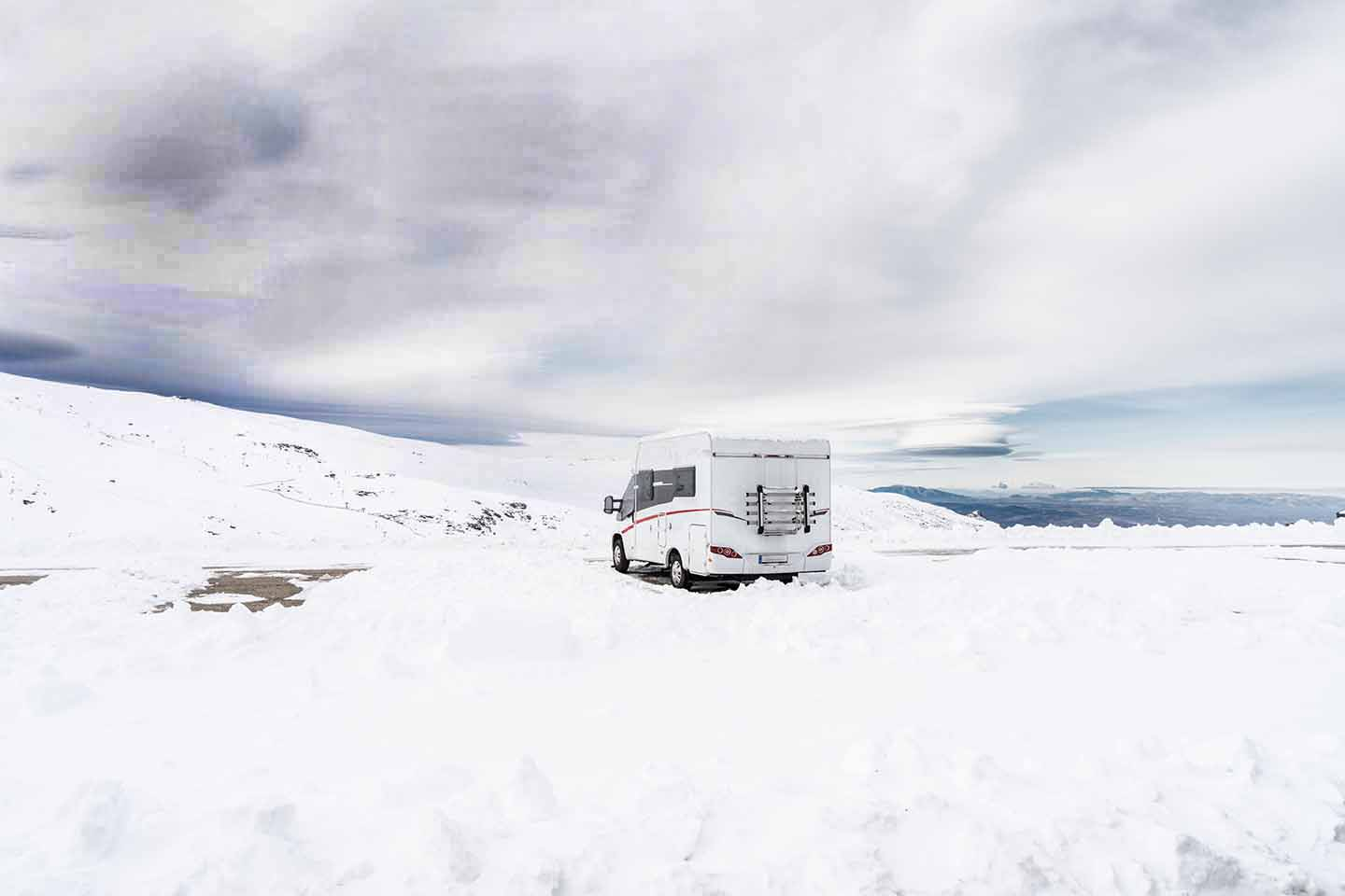 RV in snowfield under dark skies