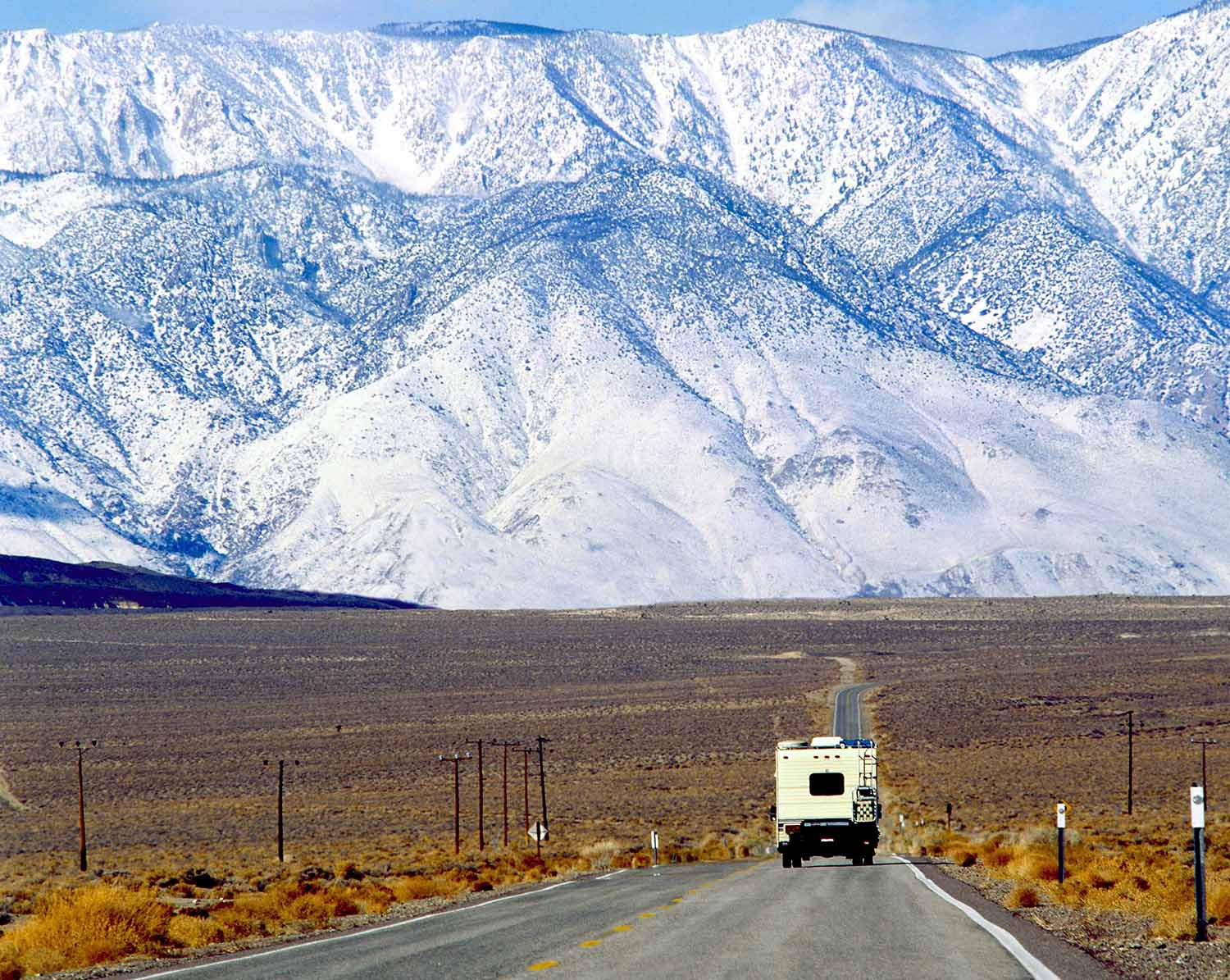 An RV heading toward snowy mountains in the background.