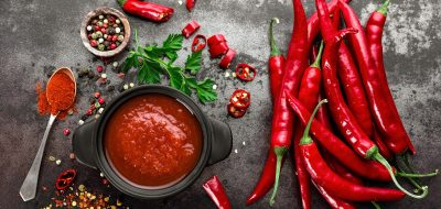 Spicy chili sauce, ketchup, red chilis on dark background