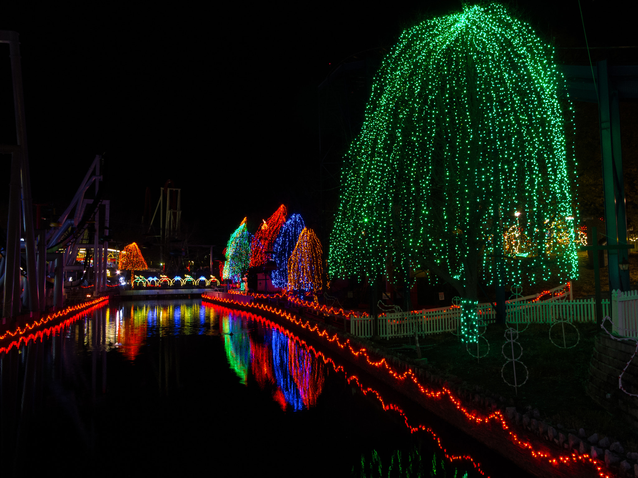 Holiday lights on trees reflected in a narrow stream.