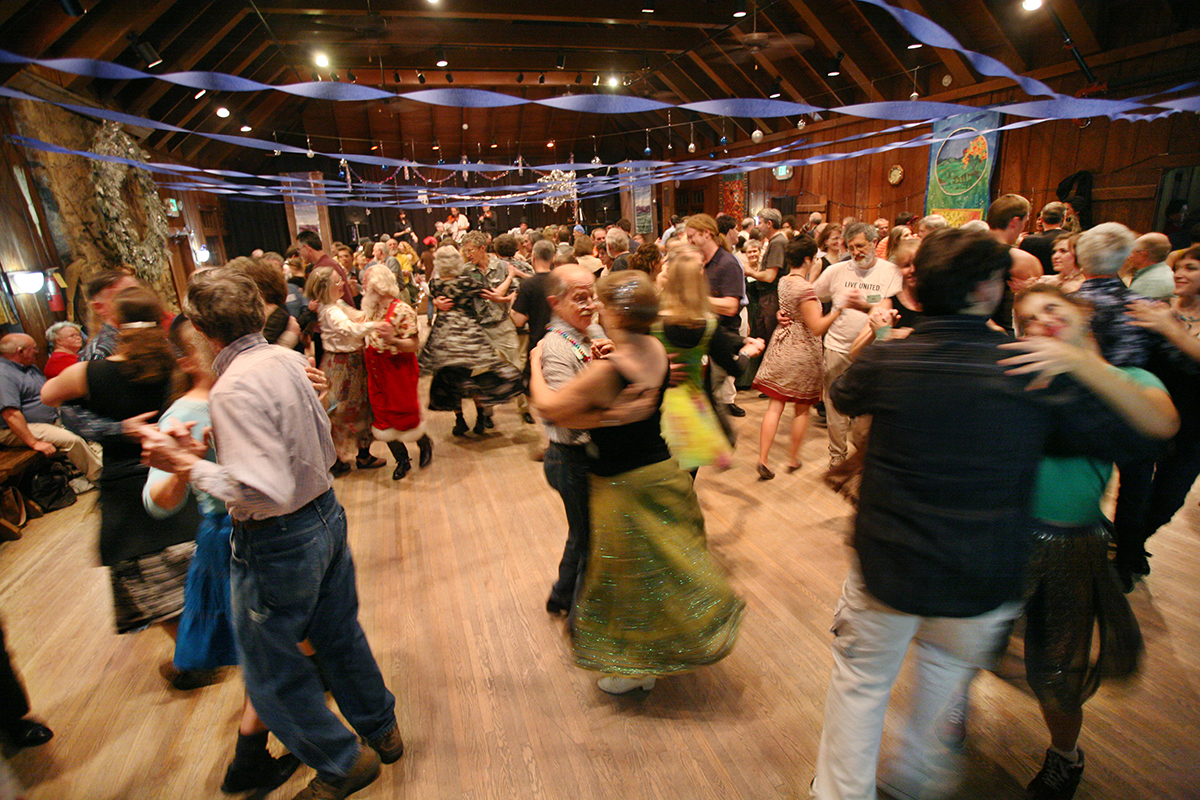 People square dancing in a barn.