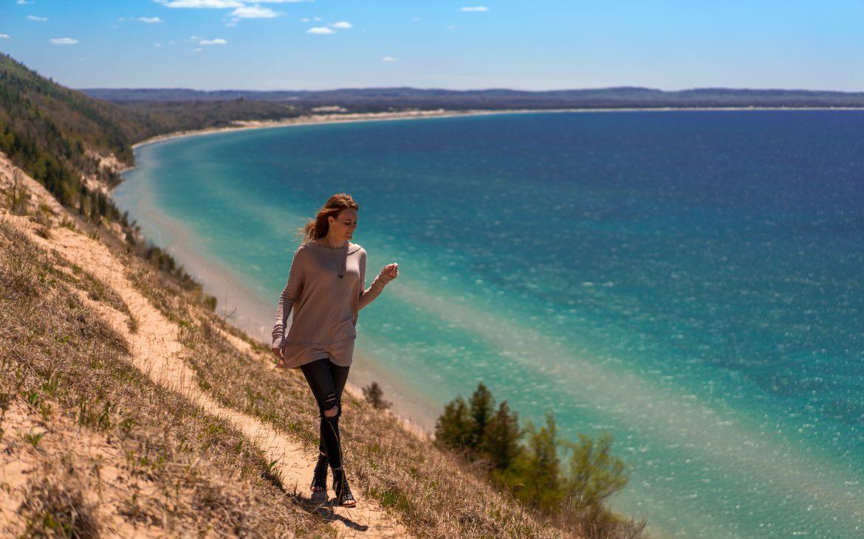 Young woman walking along dirt path of Sleeping Bear Dunes
