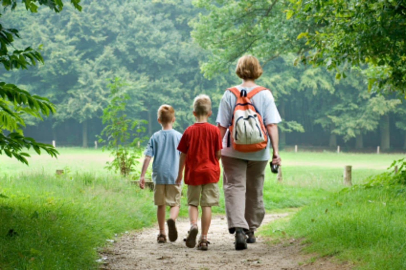 Three kids heading down a trail.