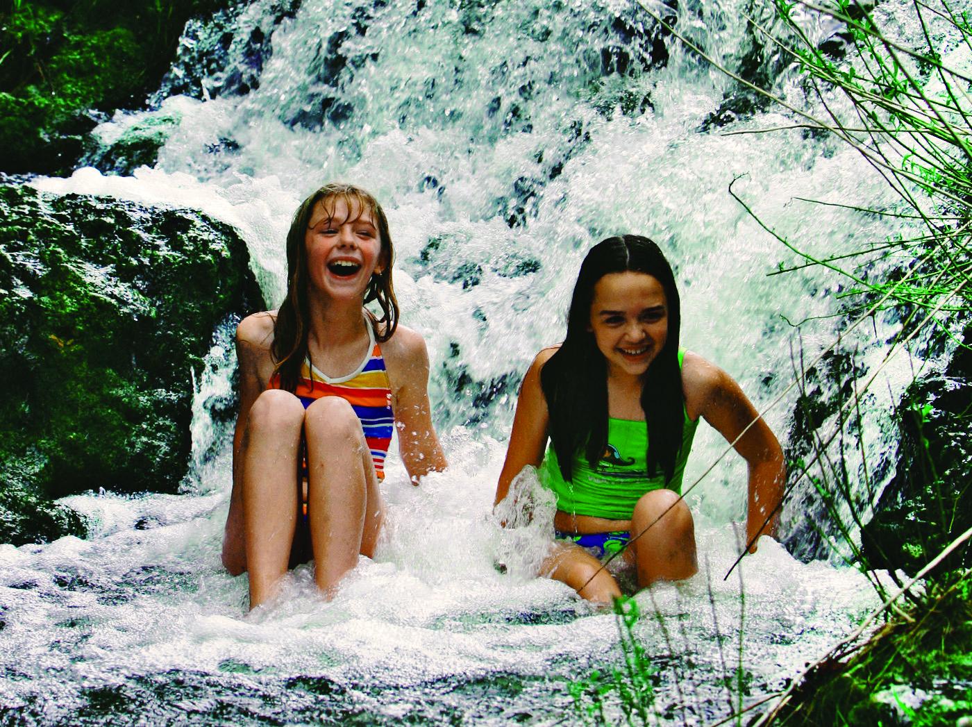 Two kids splashing in a waterfall.