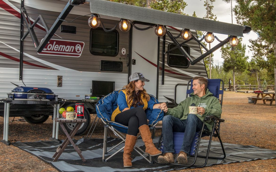 Couple sitting on chairs in front of RV