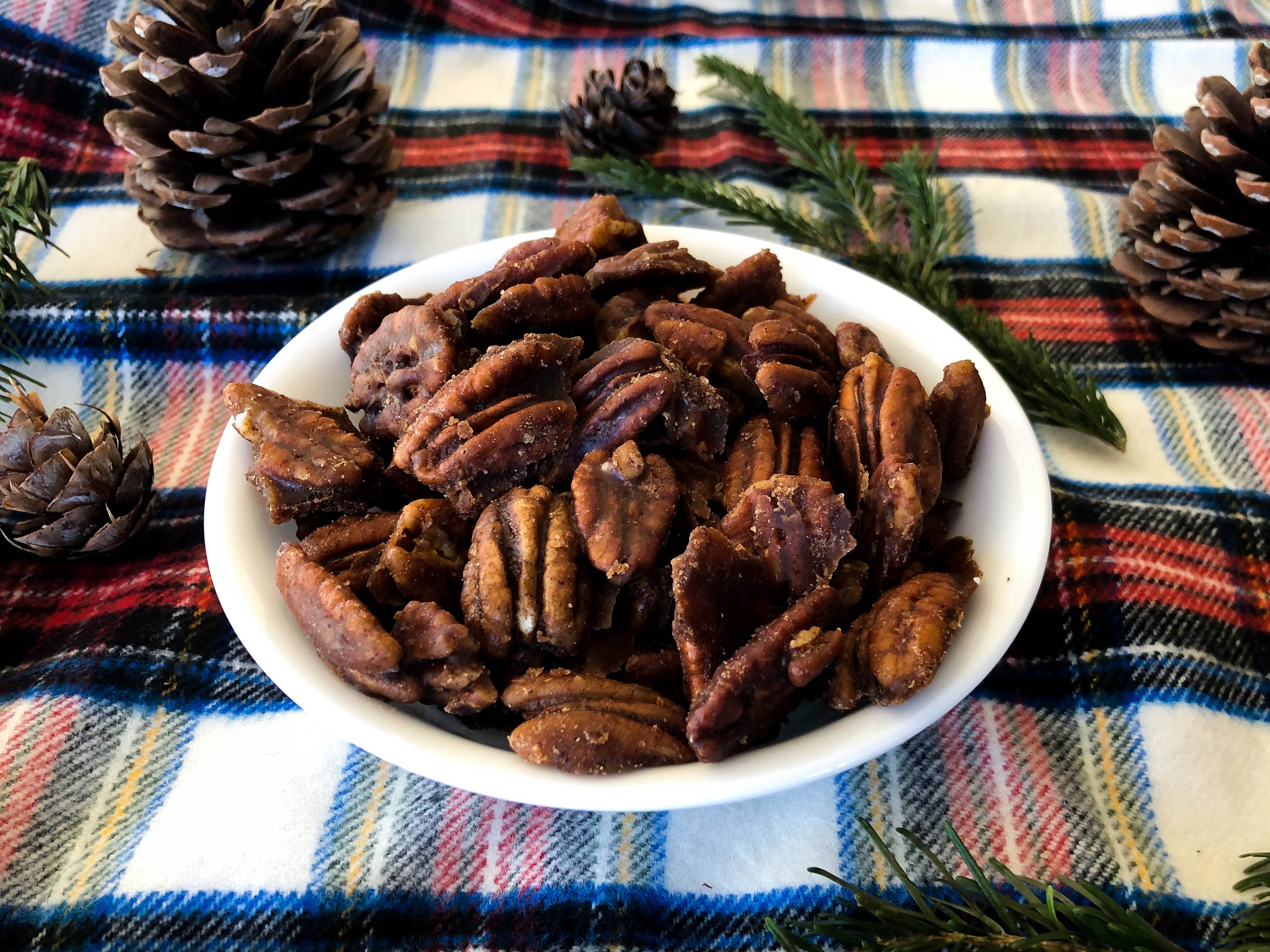 coated pecan nuts piled into a small white bowl