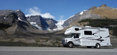 Class C motorhome with mountains in background.