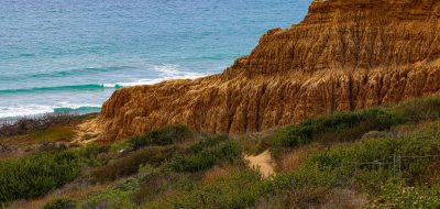 Beach Hikes in Southern California trail leads past a sandstone outcropping toward the sea.