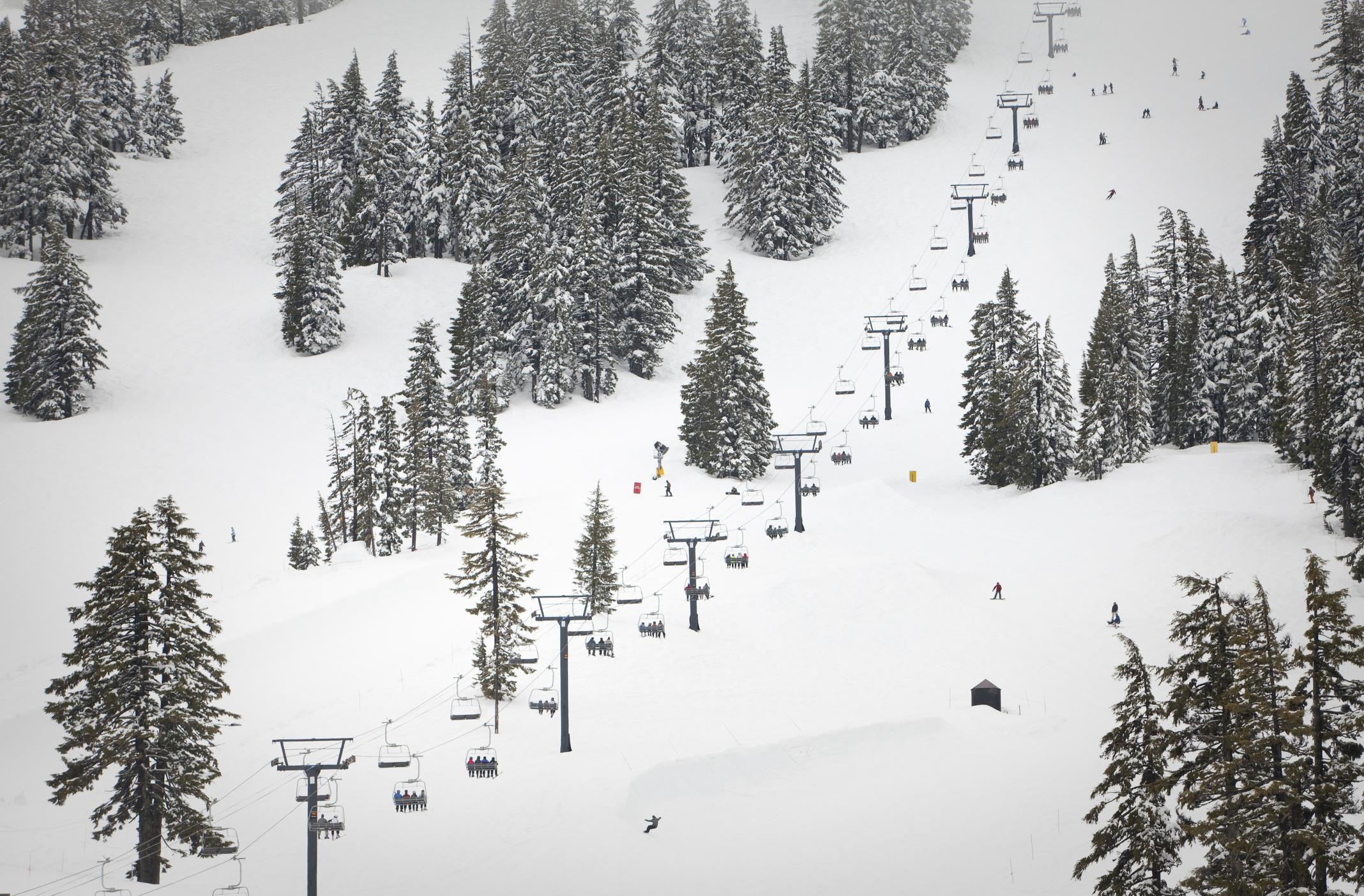 A busy ski lift ascending a slope on a hazy day.