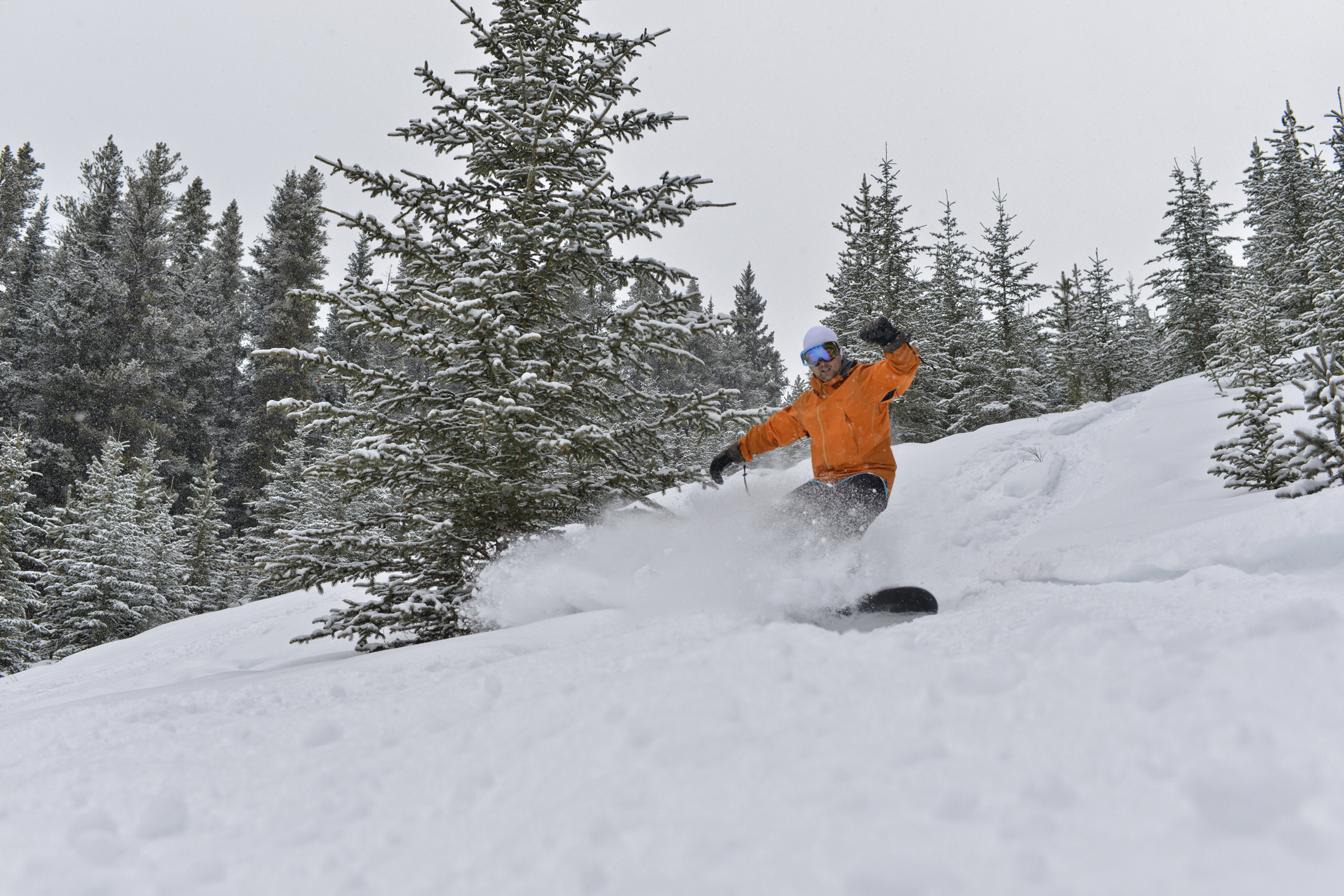 A snowboarder in an orange jacket hurtling down a slope.