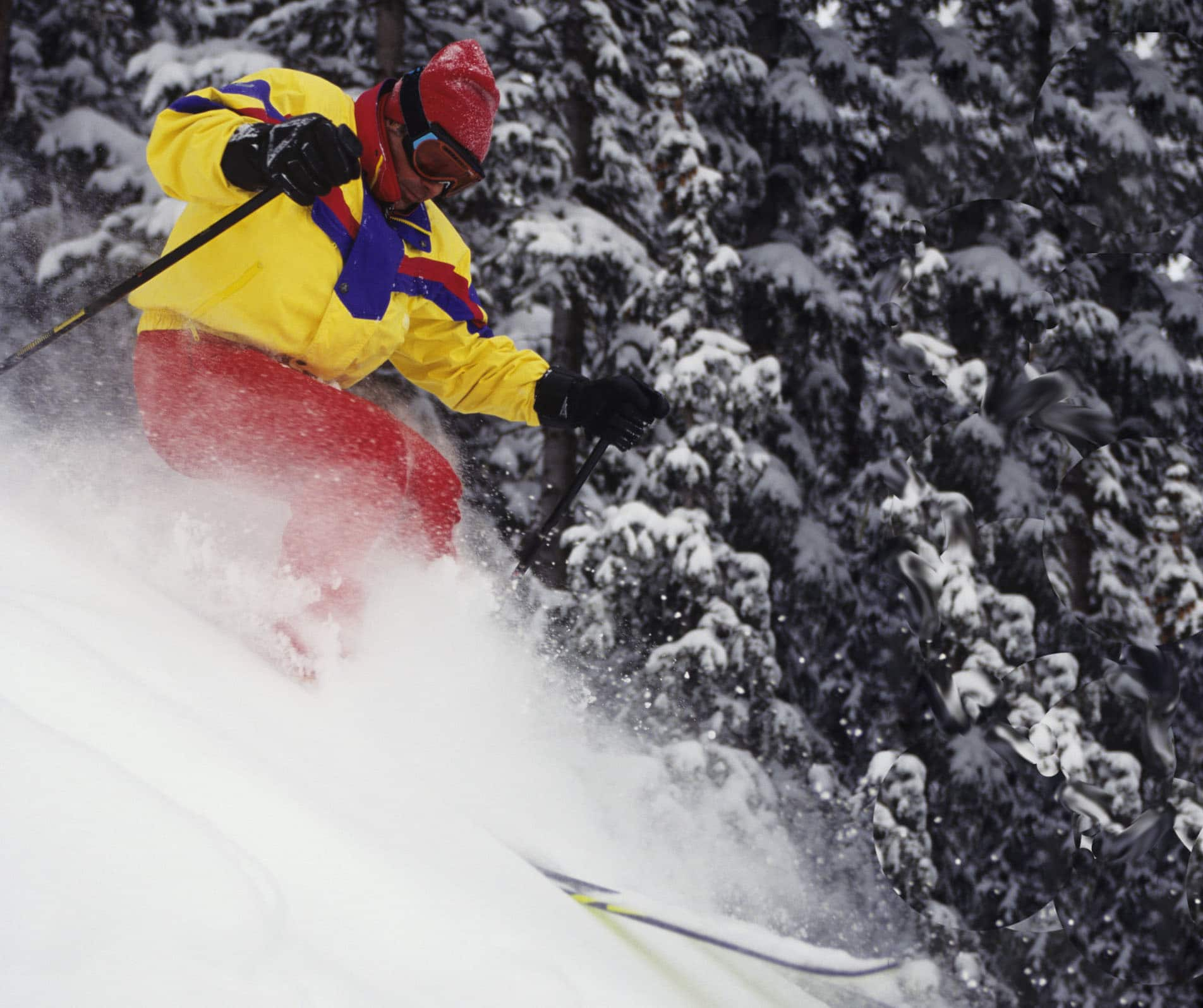 A skier in a yellow jacket traverses a steep slope.