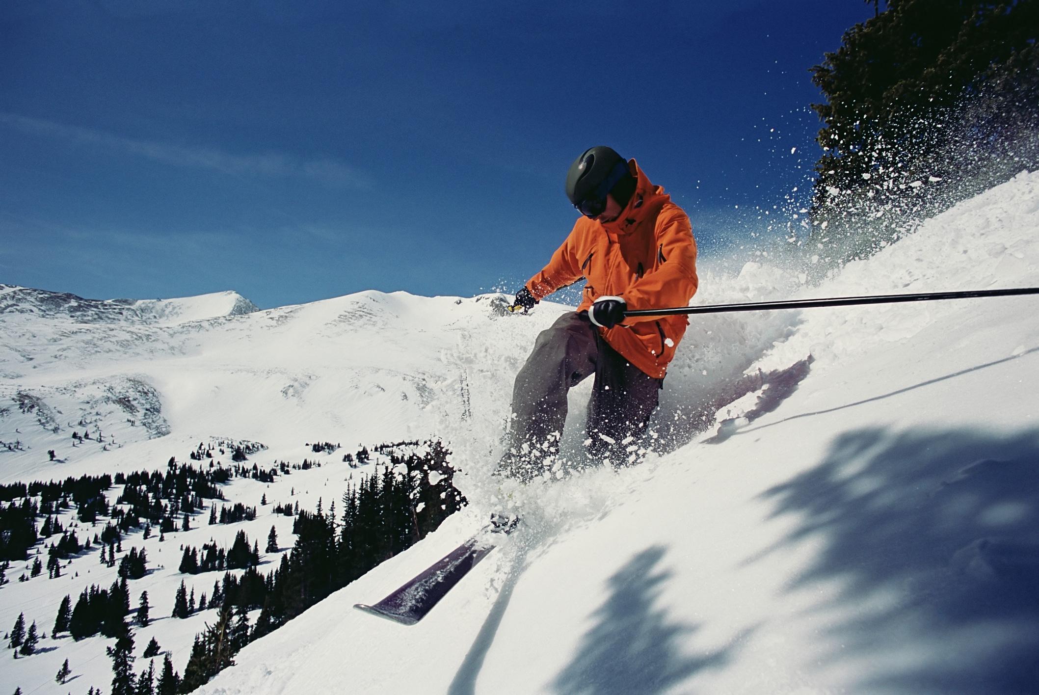 Man in orange jacket skis down steep powdery slope.