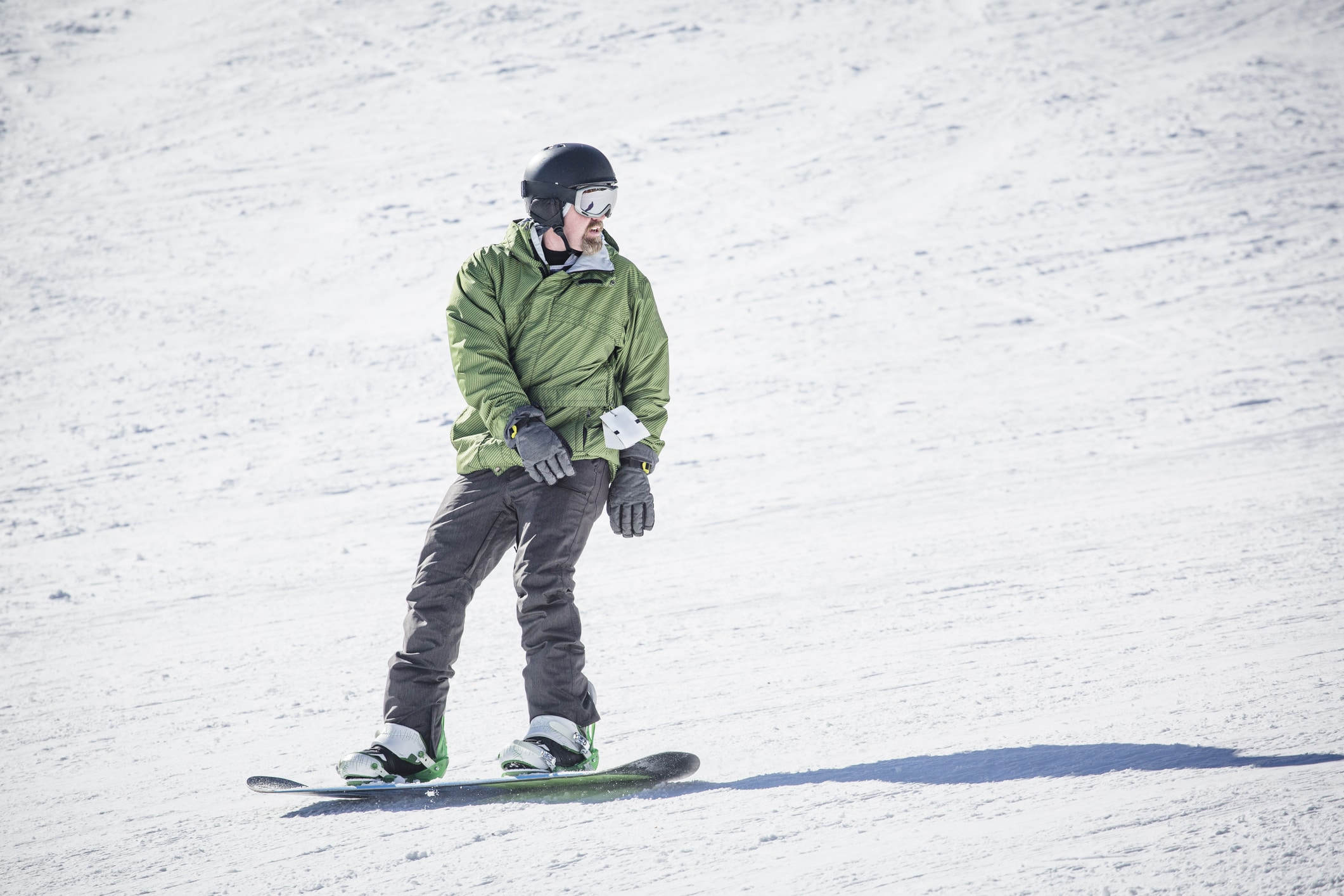 Male adult snowboarder riding down a groomed snow hill. A beautiful day on the slopes having fun