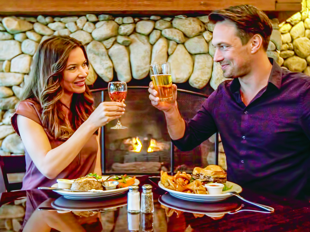 A man and woman toast glasses in front of fireplace.