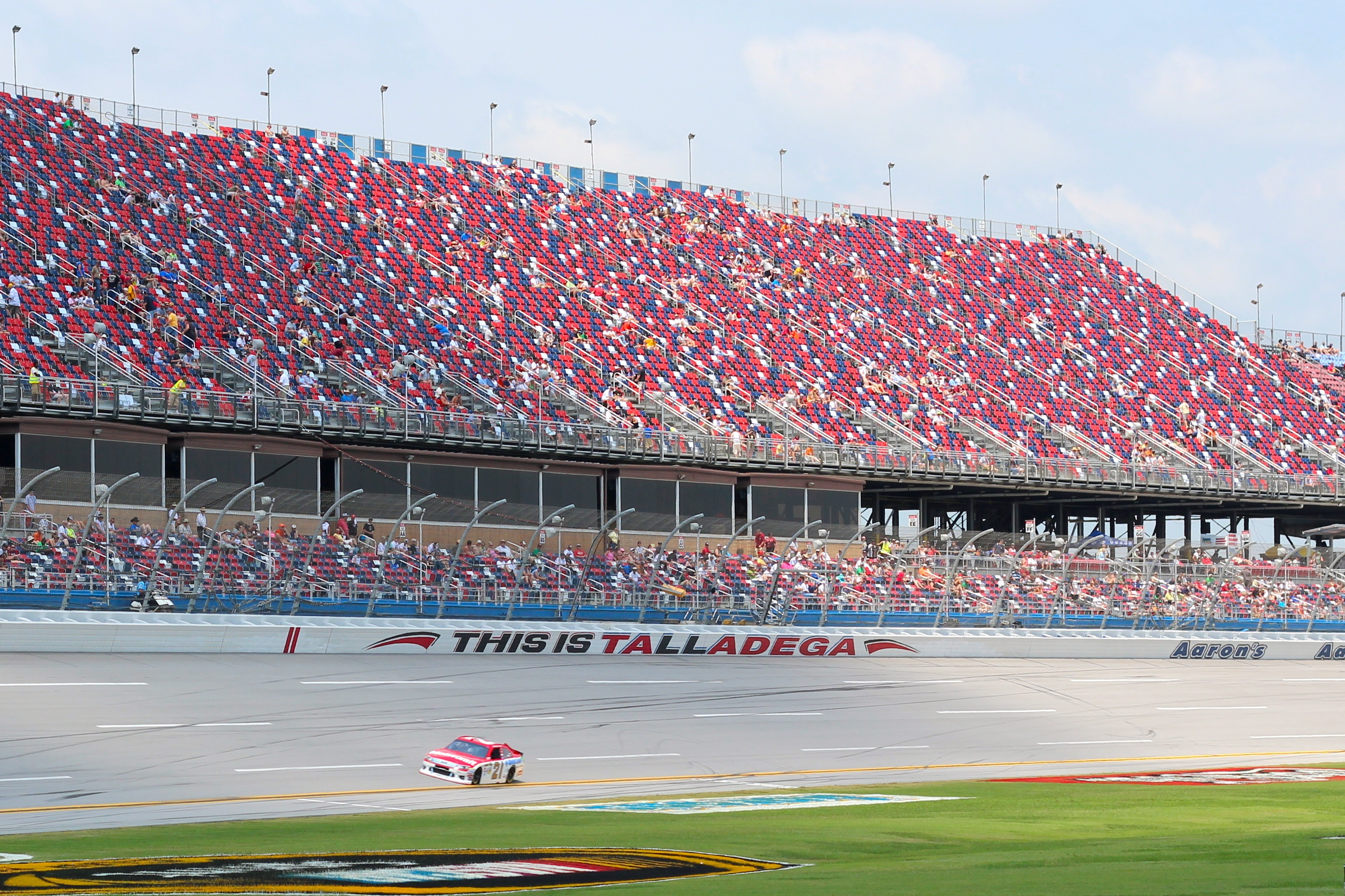 A car zooms past a red, white and blue grandstand.