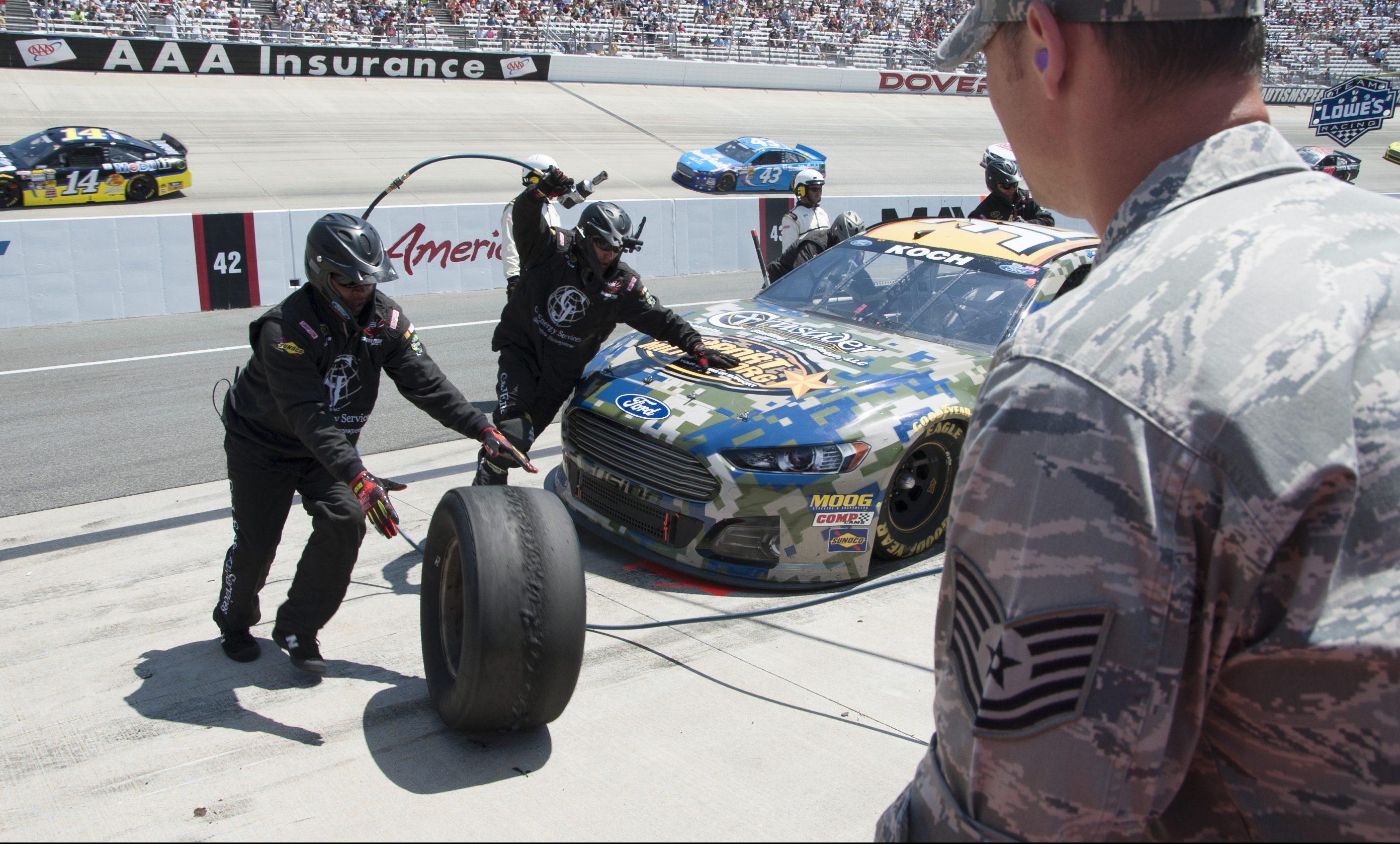 Mechanics service a car at a speedway.