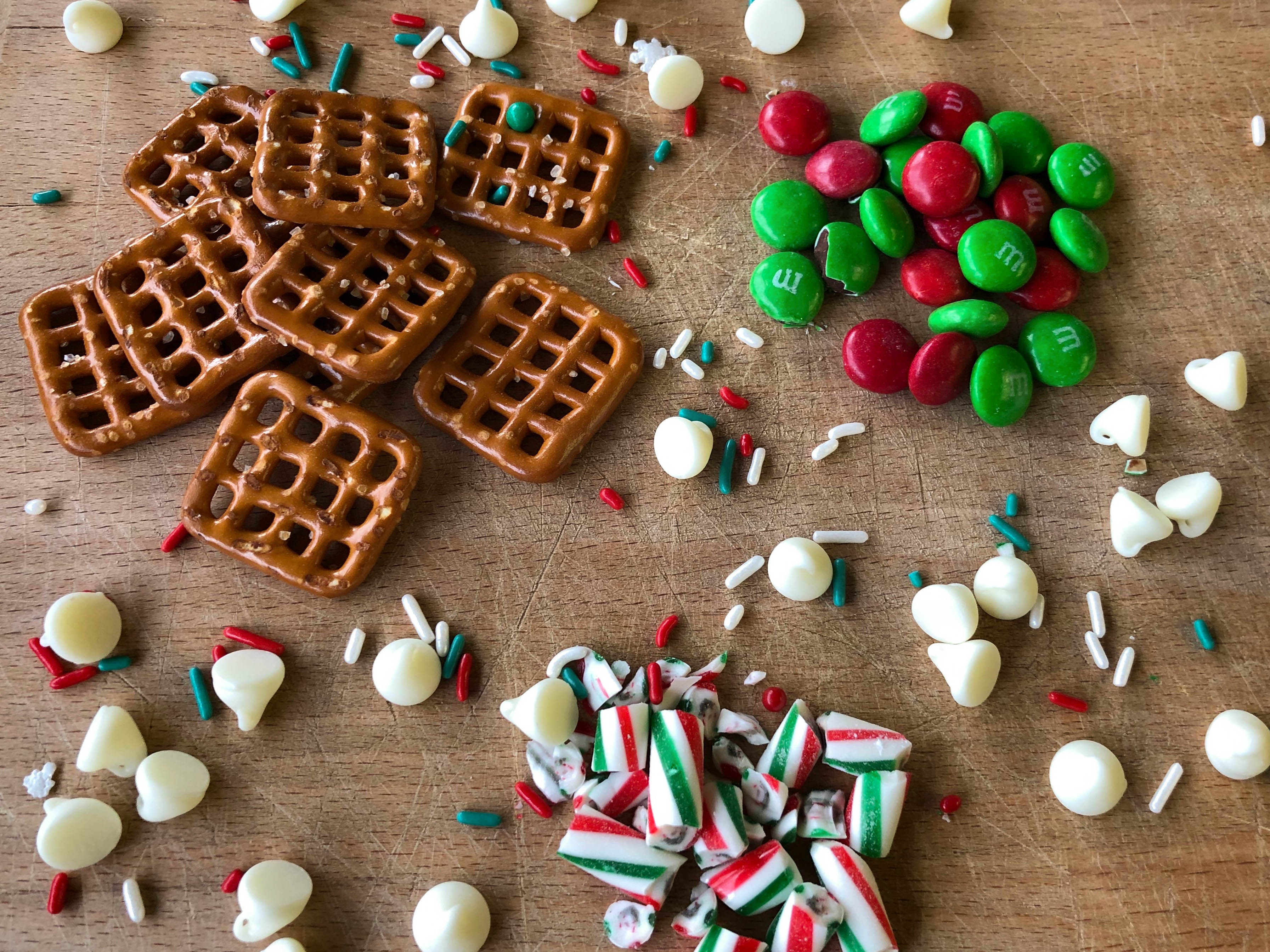 Pretzels, M&Ms and white chocolate chips on a wooden surface.
