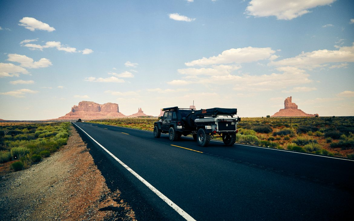 Black Jeep pulling small camper on highway through Oljato-Monument Valley