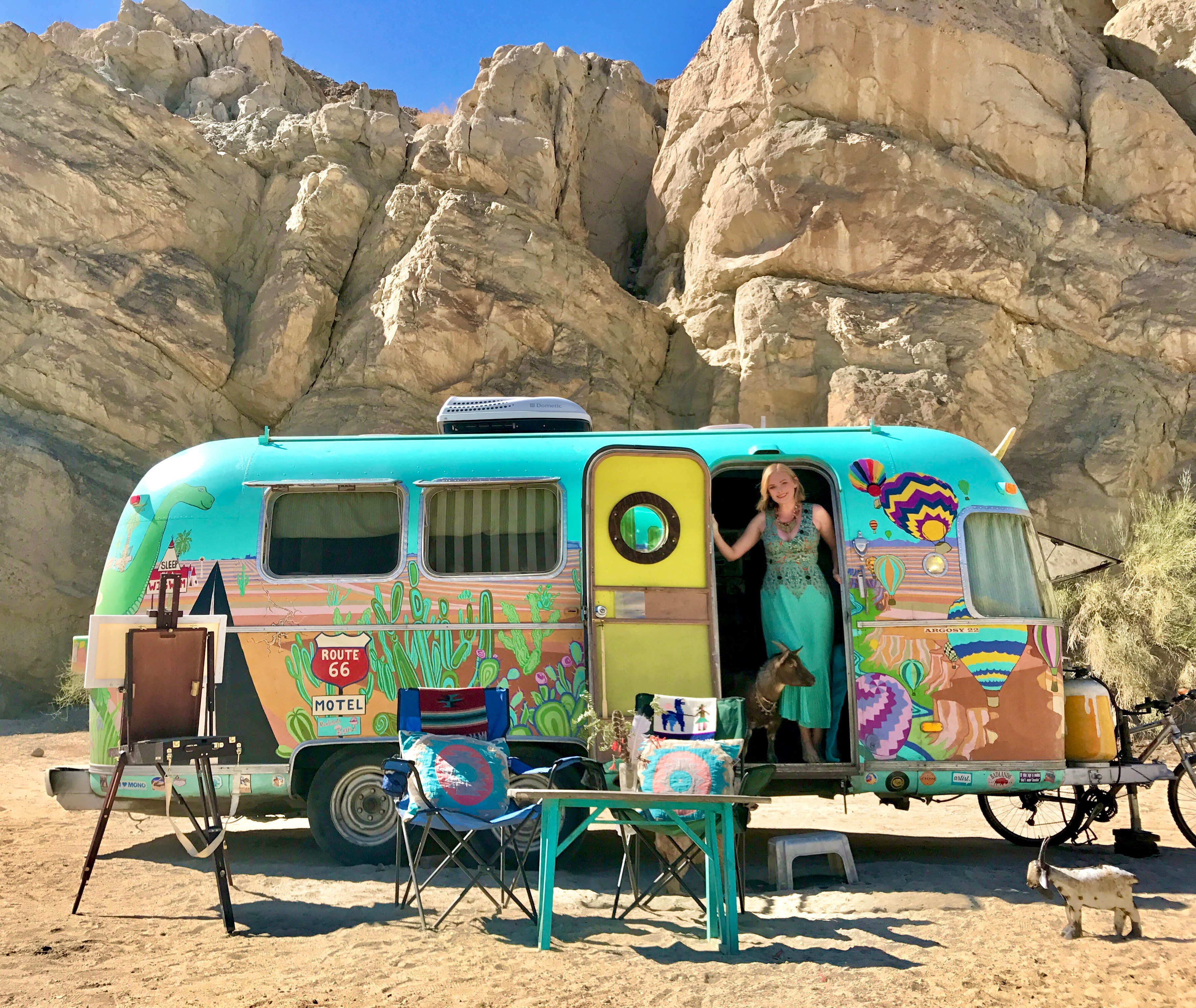 Colorful Airstream with woman standing in door.