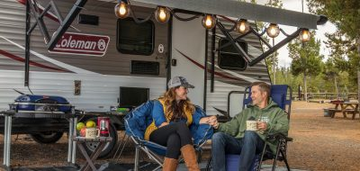 A couple in warm clothes lounge by their RV