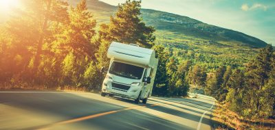 The road ahead for 2021 -- An RV driving on a forested highway with sunlight streaming through.