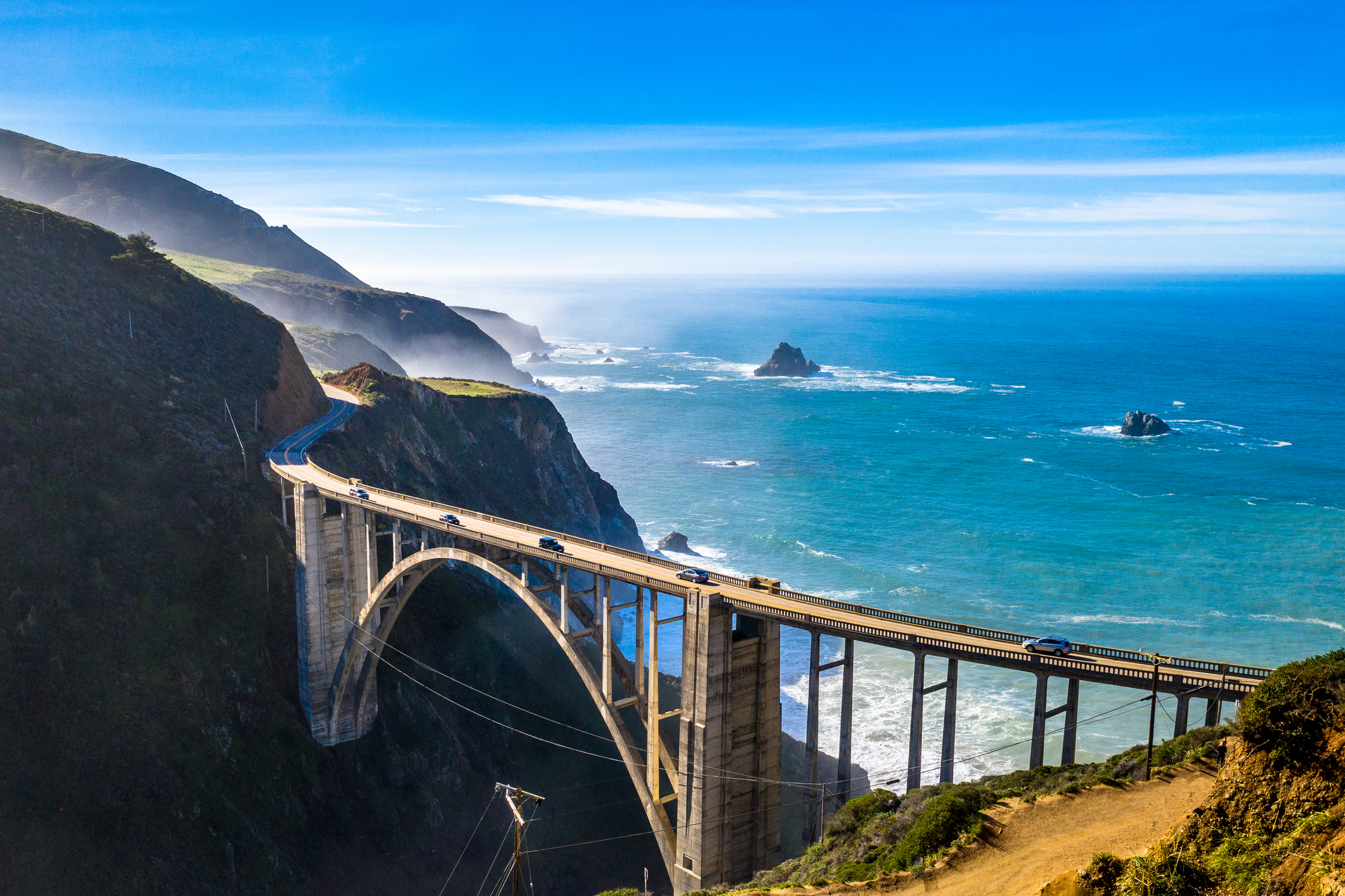 A bridge crosses a canyon with ocean in backgroud.