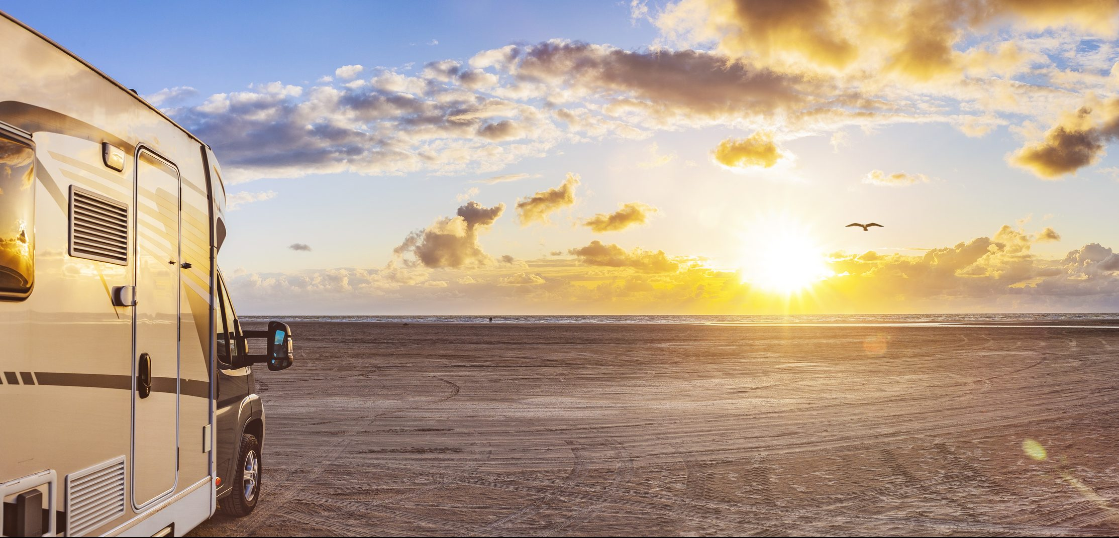 Motorhome facing the ocean at sunset