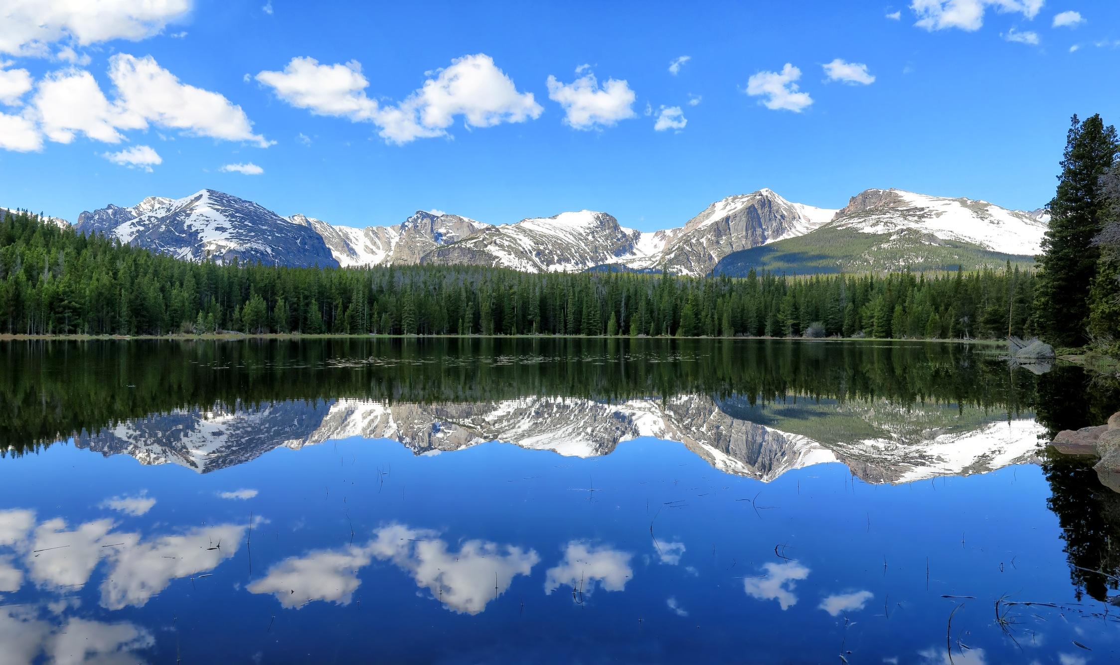 A lake reflects a snowcapped mountain range