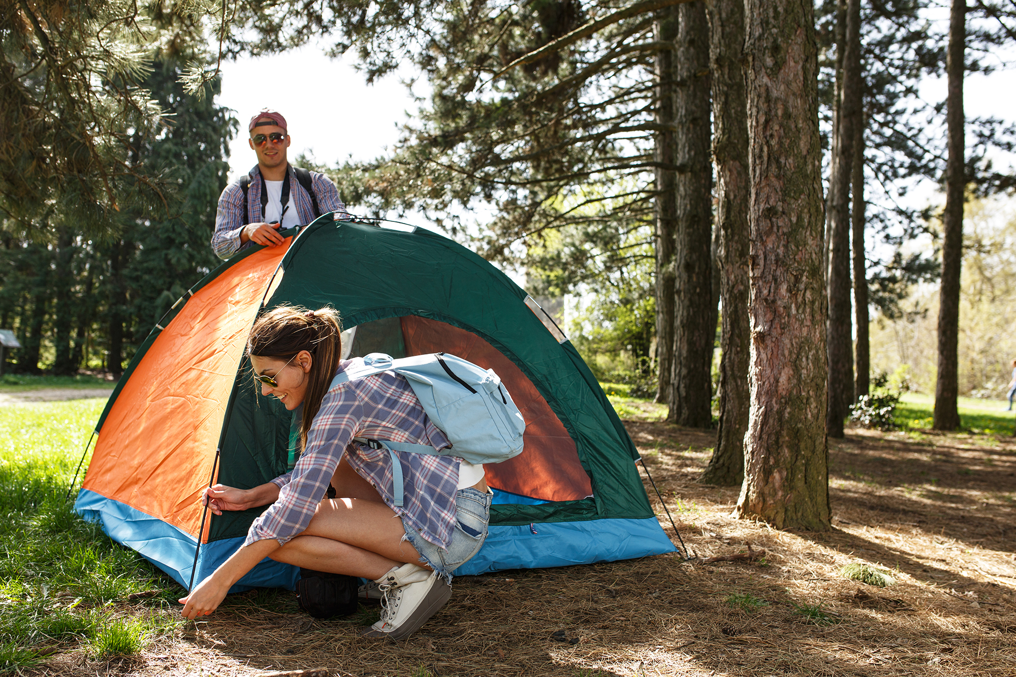 A man and woman setting up a tent in a grassy clearing