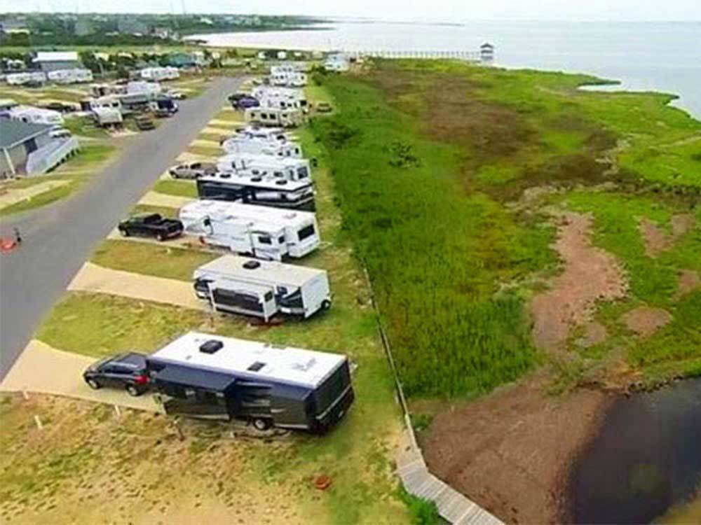 RVs parked diagonally along a coastline