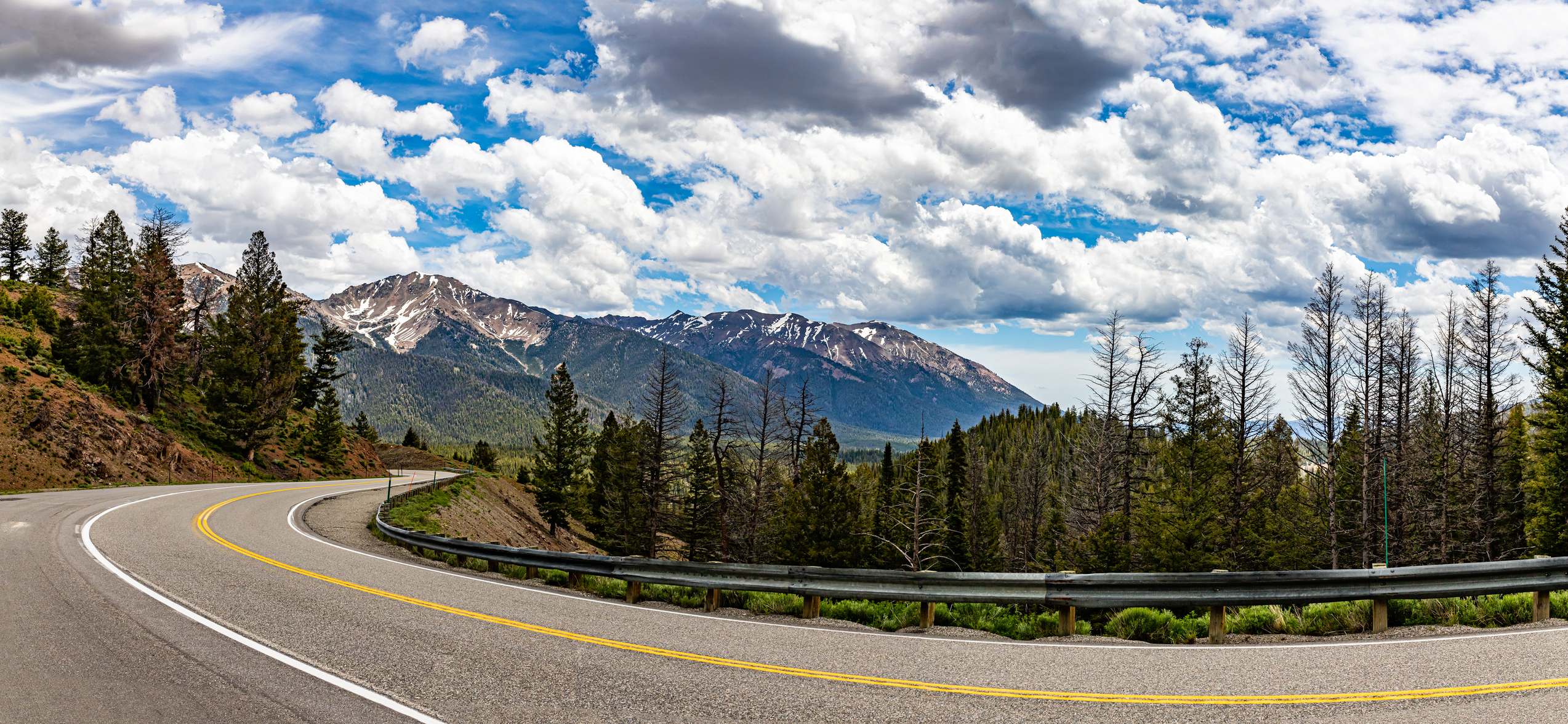 A highway curves through a forested landscape.