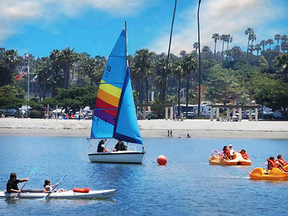 Sailboats and kayaks on a bay offshore of an RV resort.