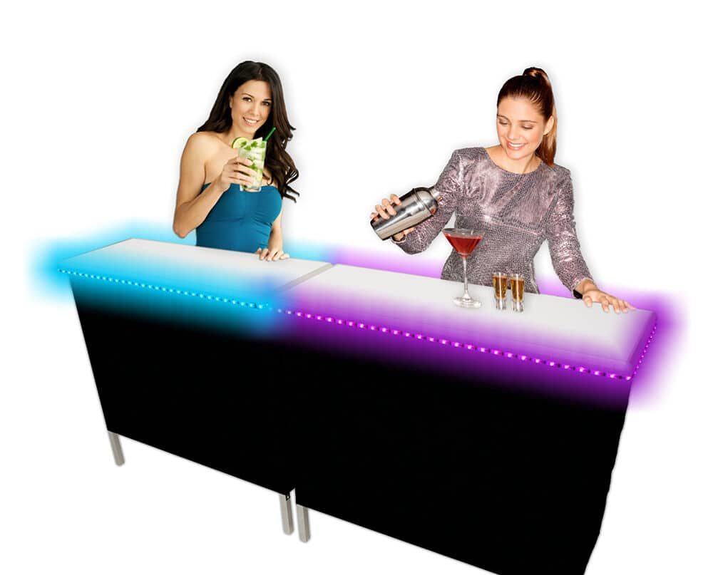 Two women pouring drinks over a lit-up bar.