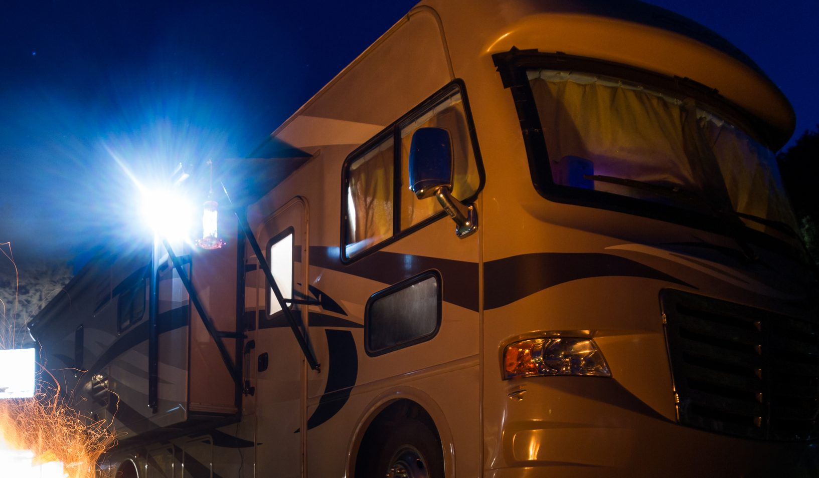 A motorhome during the evening with fire and light.