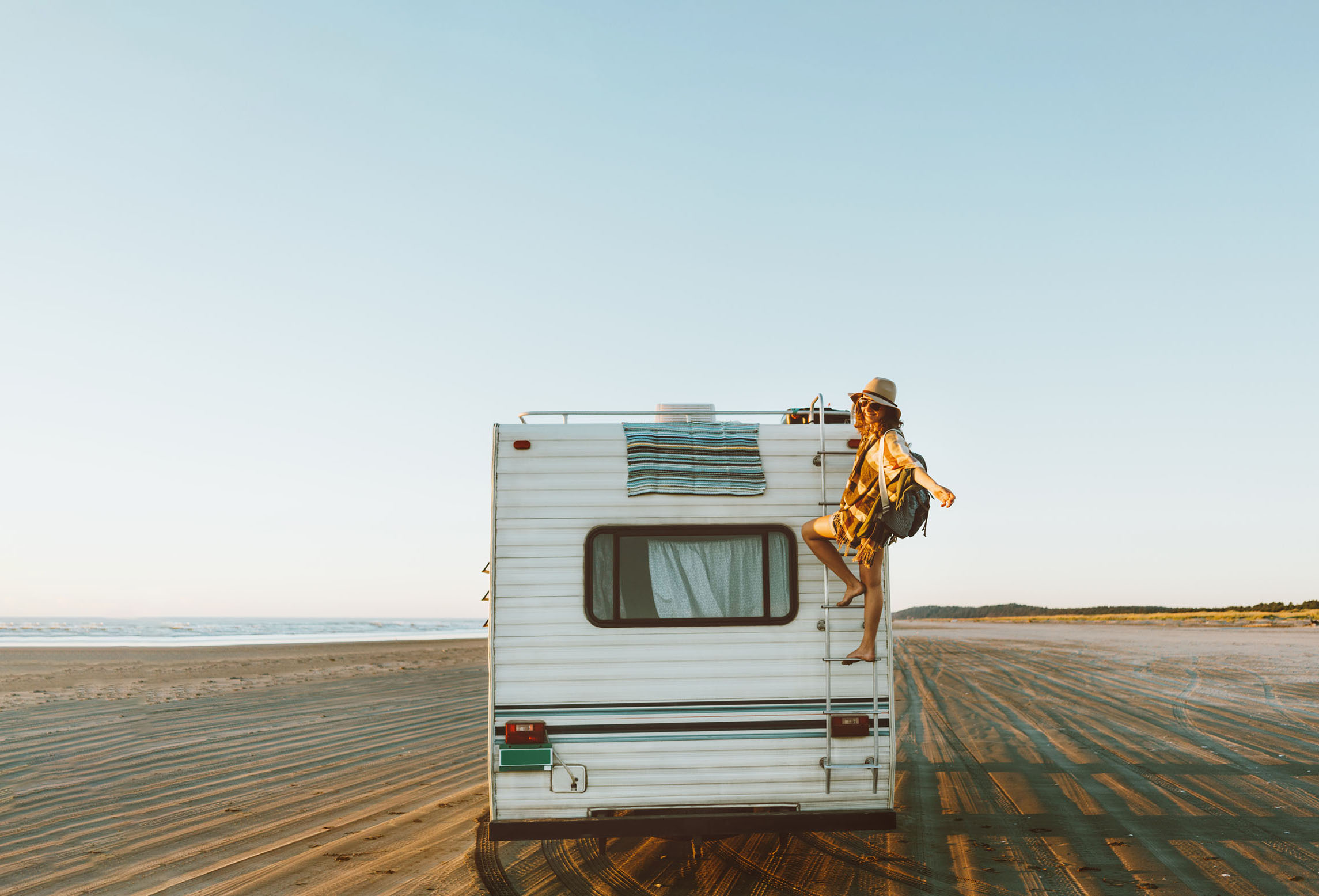 Woman climbing on roof of RV
