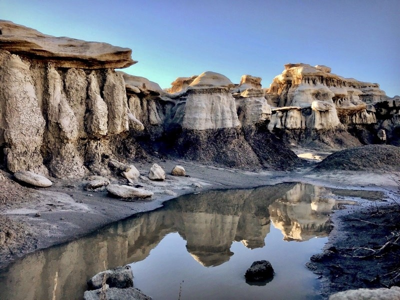 Mushroom-like rock formations overlook a placid wash.