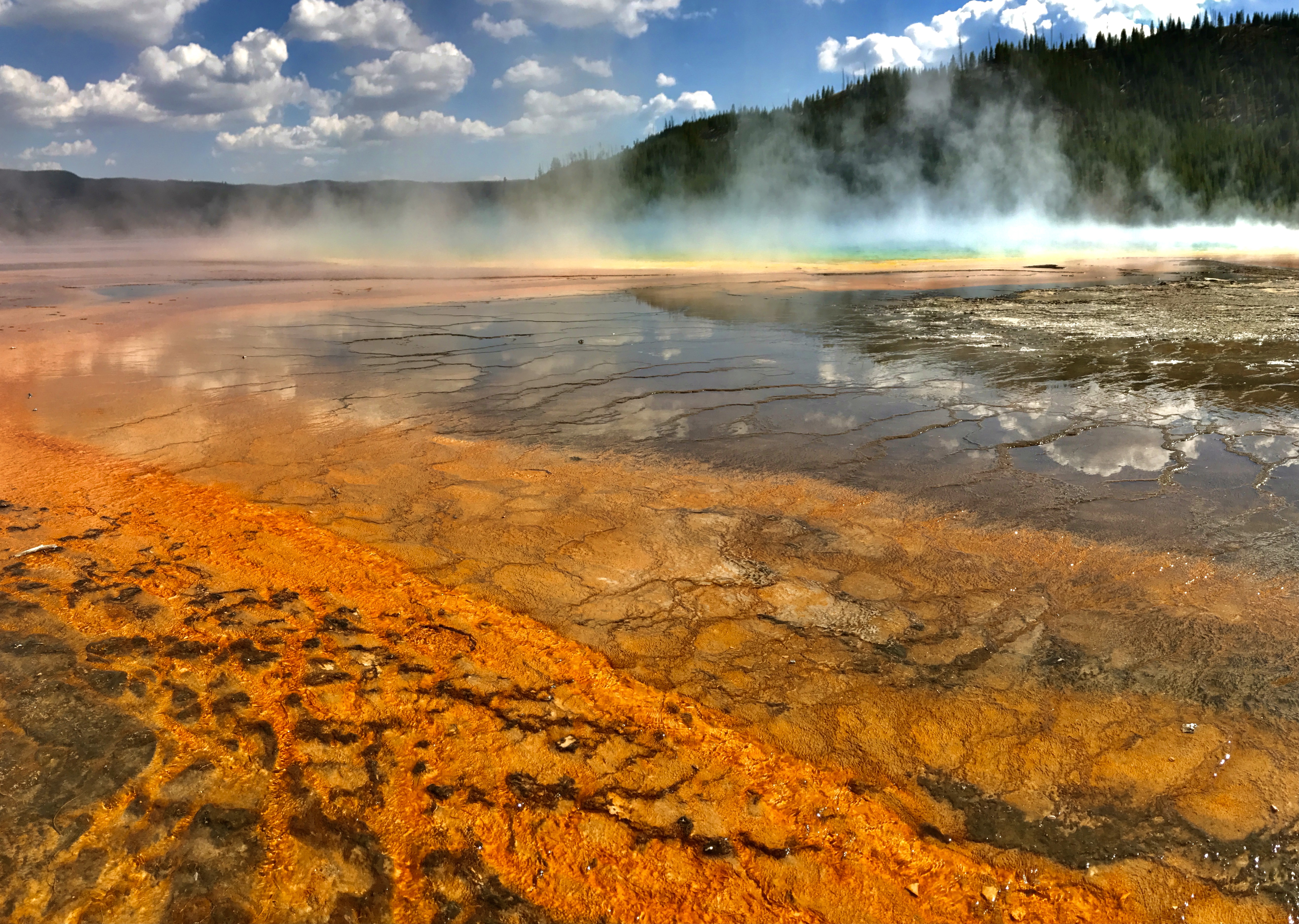 Steam rises from a shallow pool of water with a rust-colored bottom.