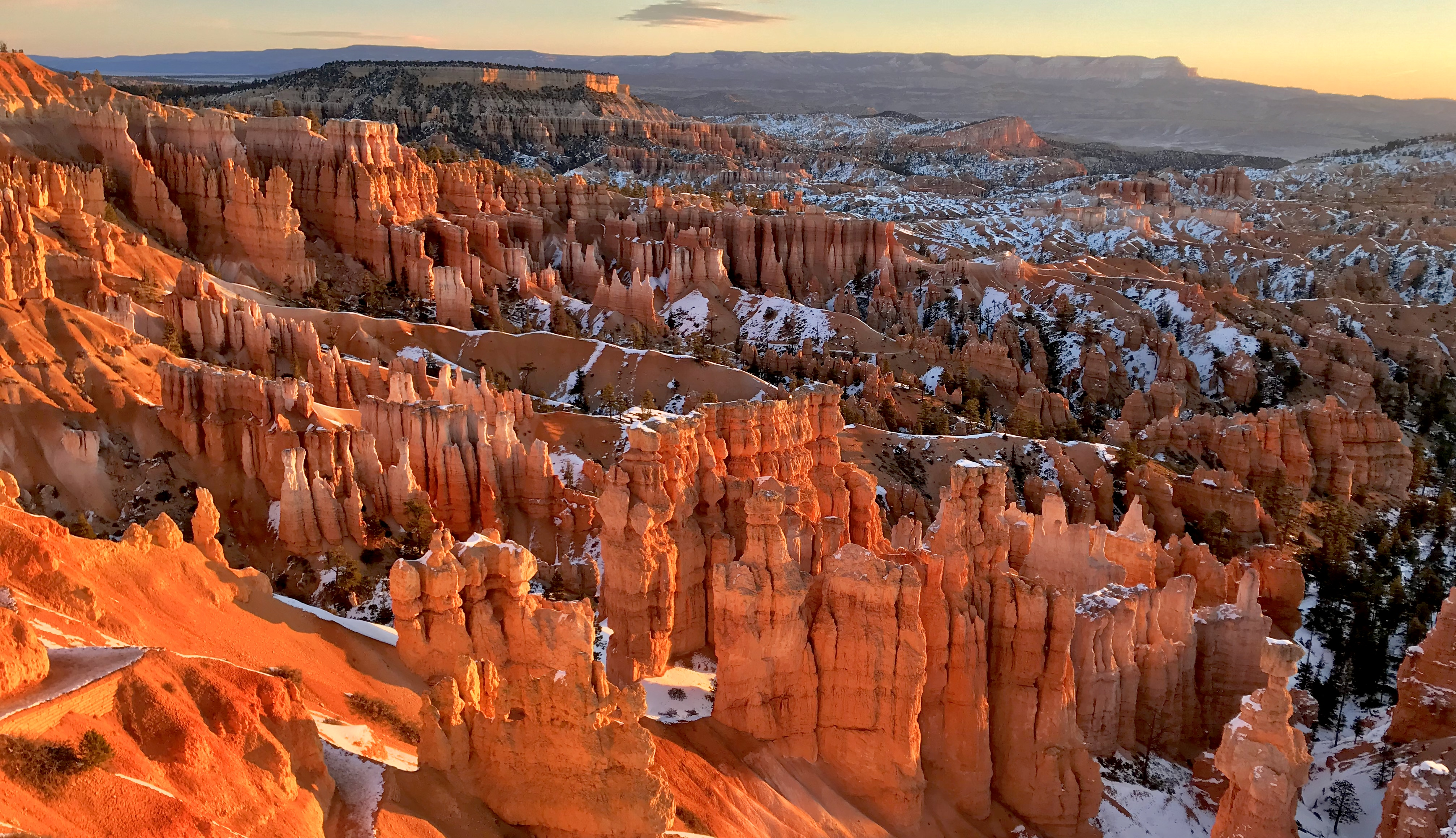 Stone hoodoos eerily rise toward the sky as morning sun bathes them in a warm red glow.
