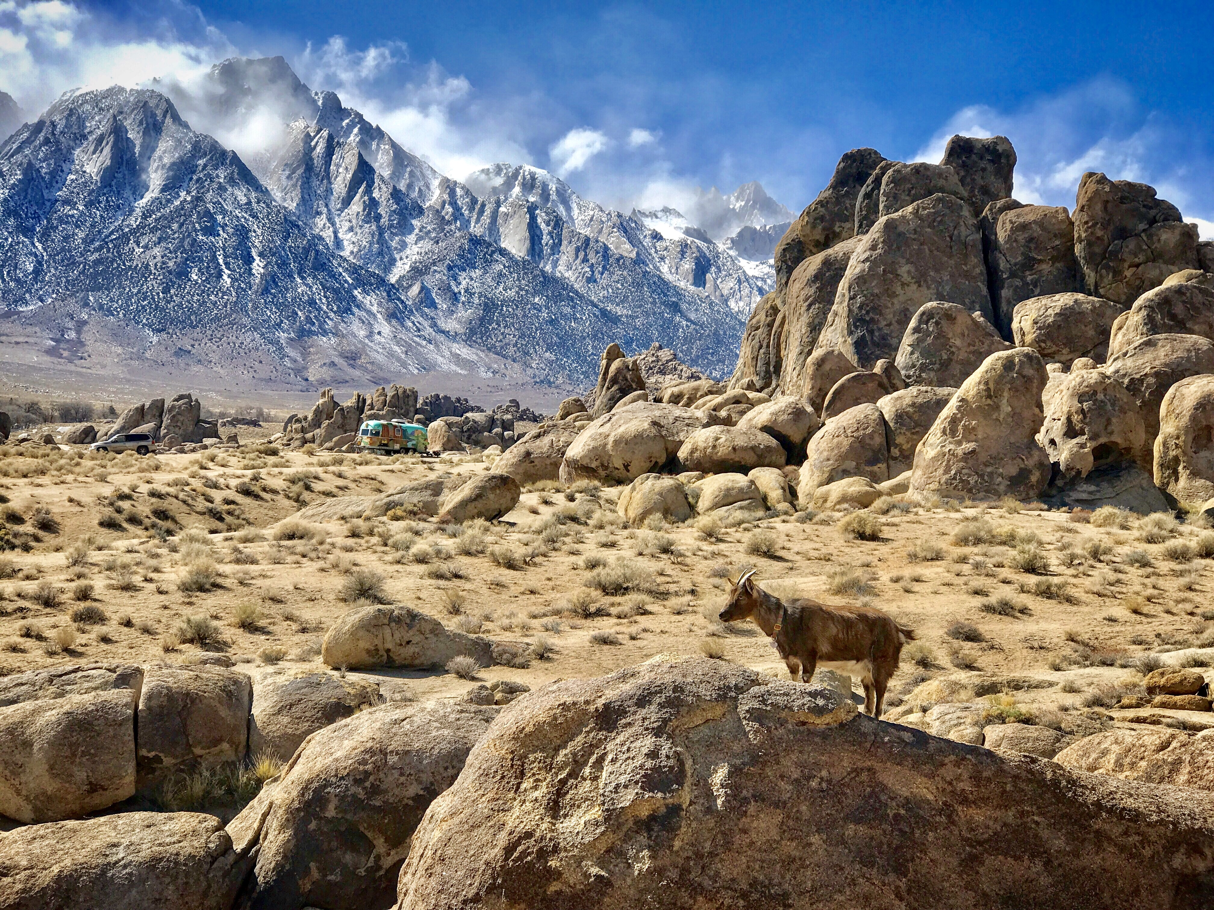 Huge, round boulders lay scattered on a landscape overlooked by high, snowy mountains.