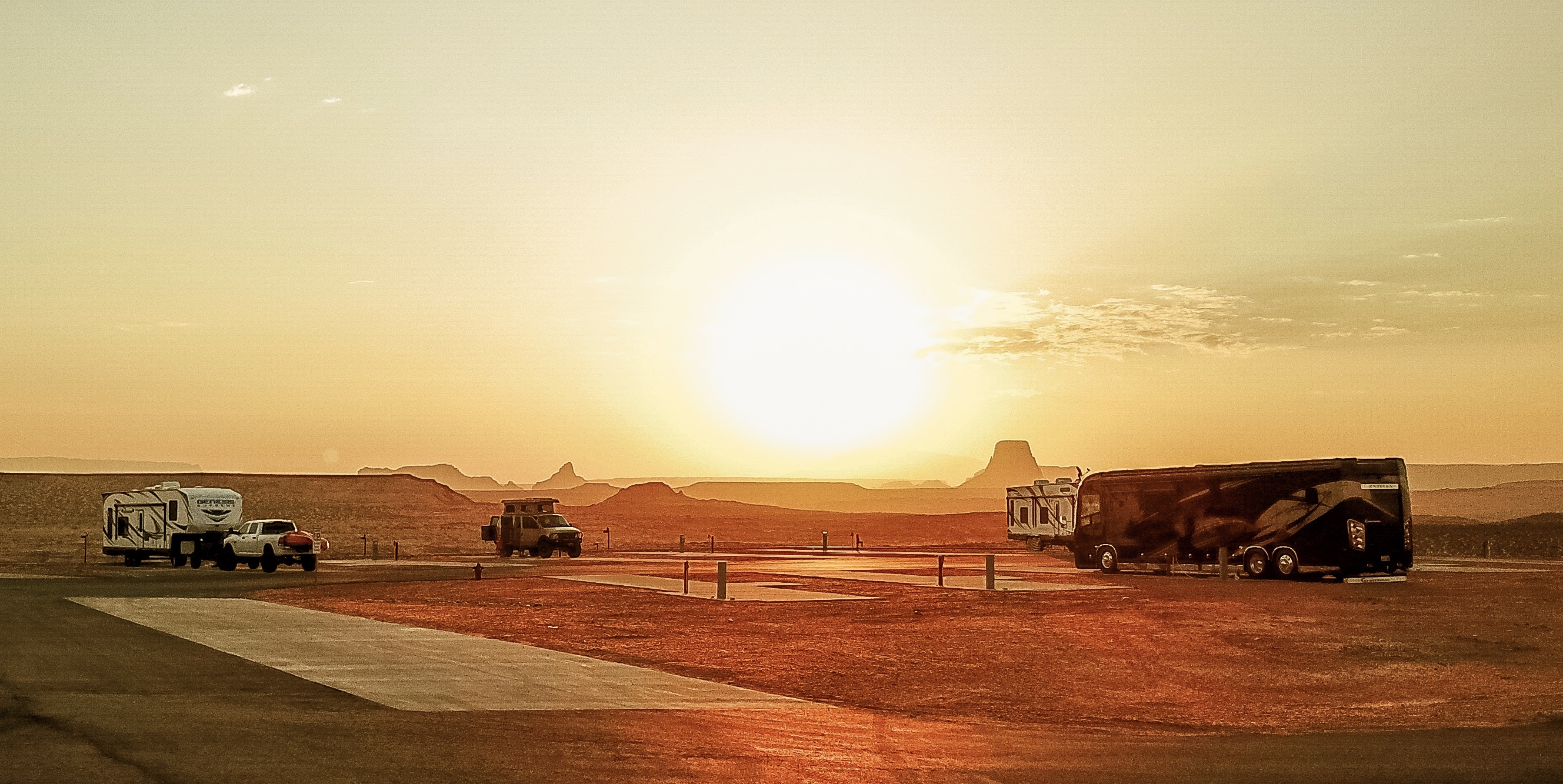 RVs parked on campsites against a desert sunset.