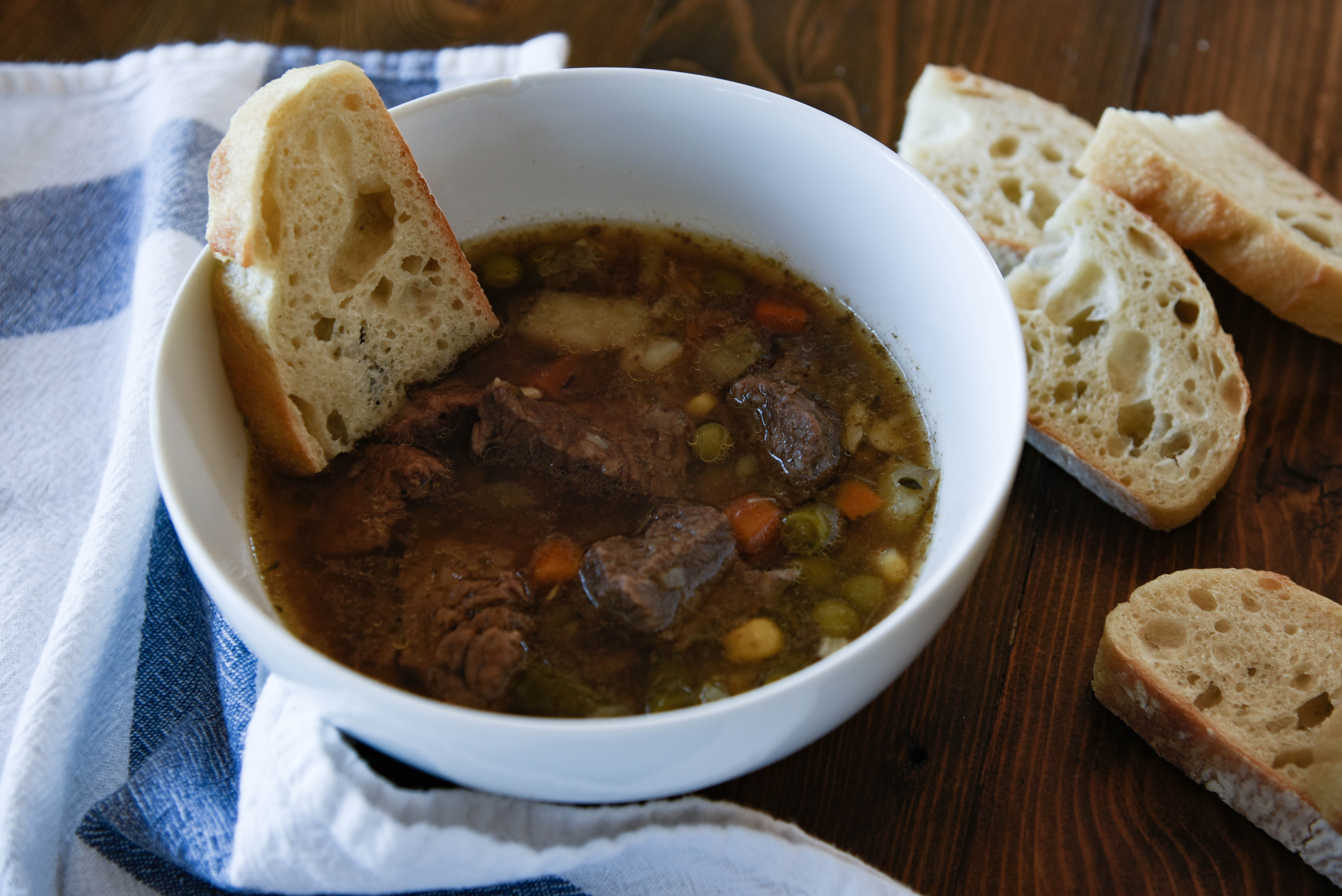 A bowl of soup with bread dipped in it