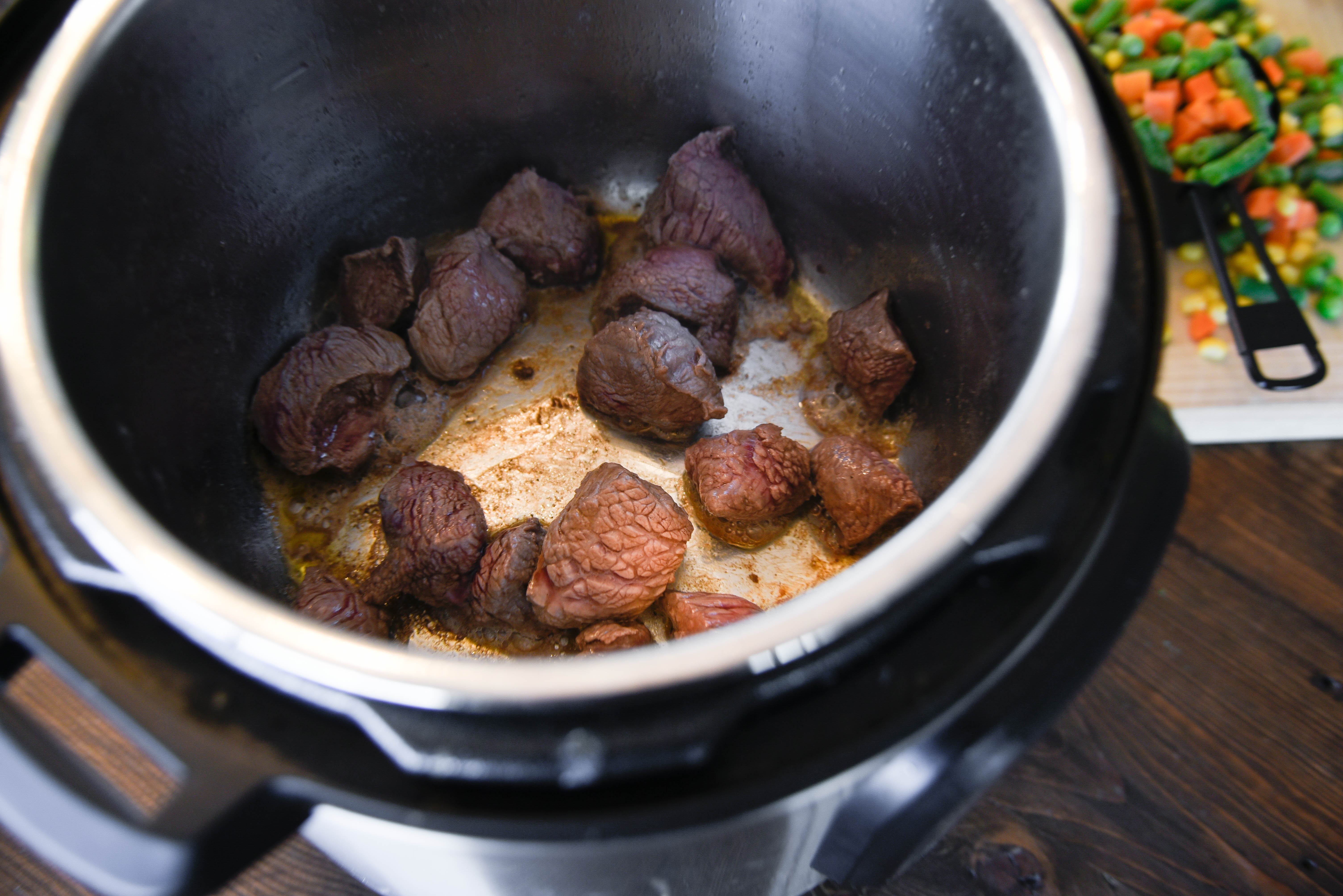 Chunks of beef sizzling at the bottom of a pressure cooker.