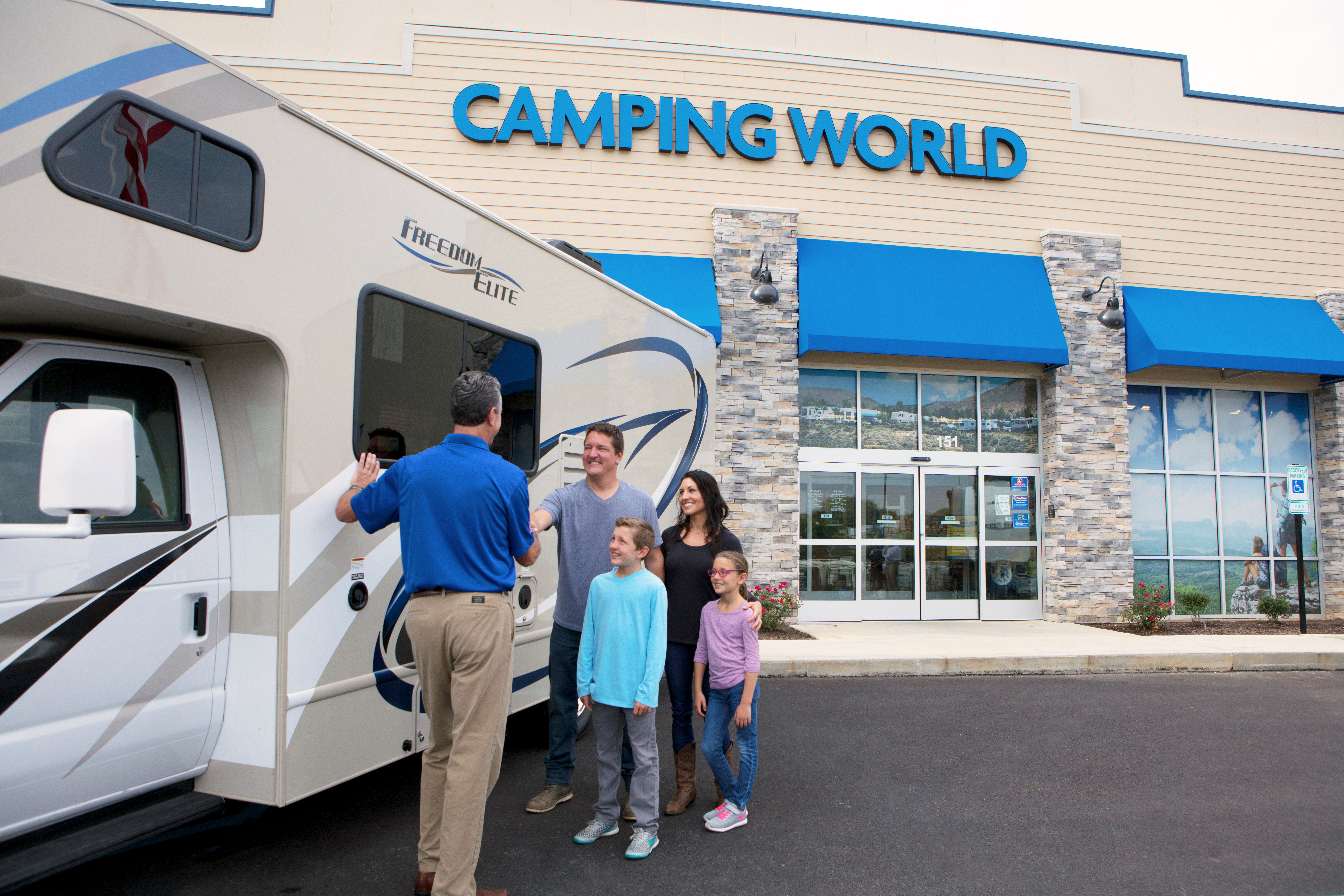 Buying a new or used RV A family smiles as they purchase a Class C motorhome