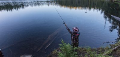 a man casts a line in a scenic lake