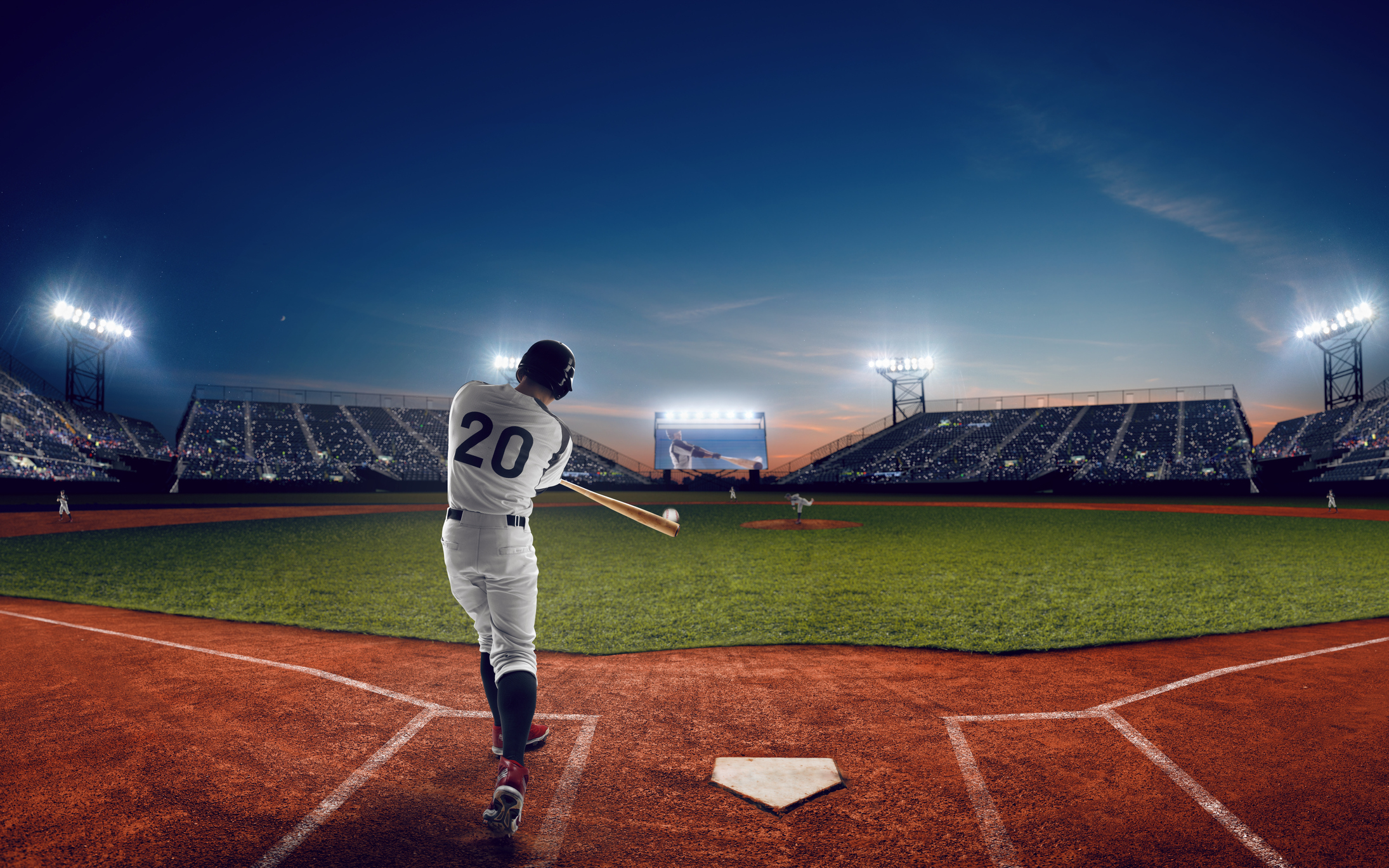 A baseball hitter swinging with view toward the outfield