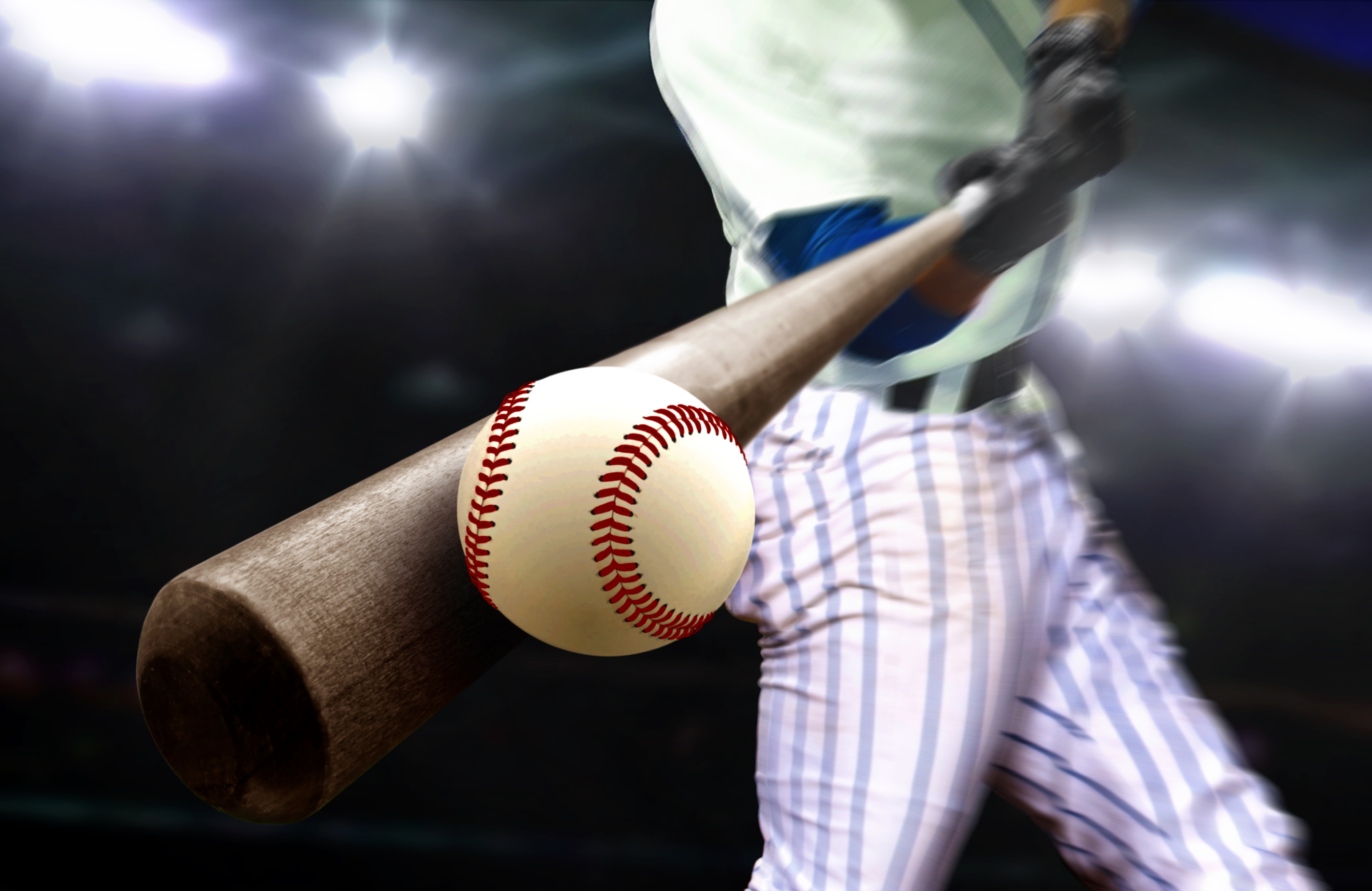 Baseball player swing hitting ball with bat in close up under stadium spotlights