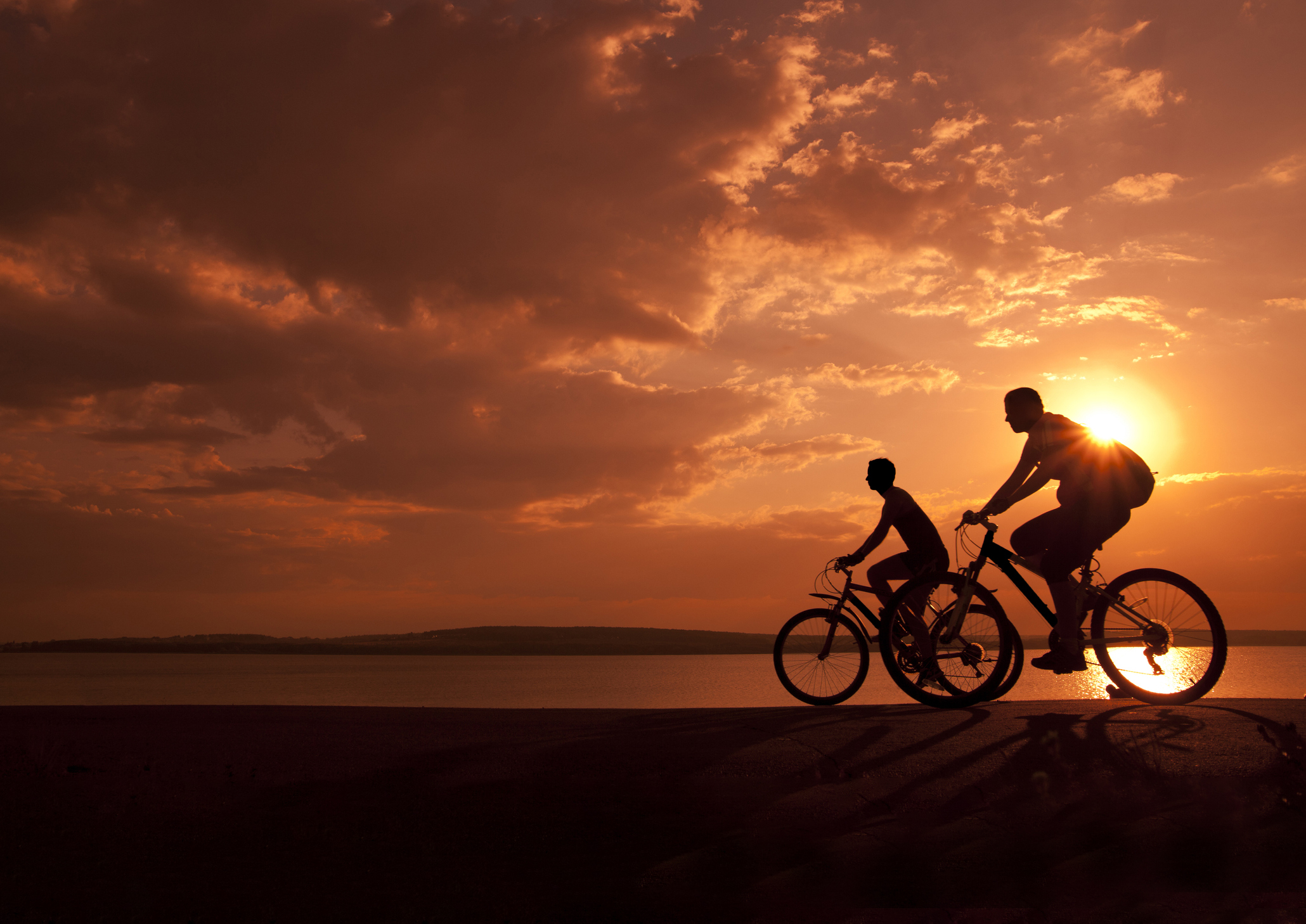 A pair of riders during sunset.