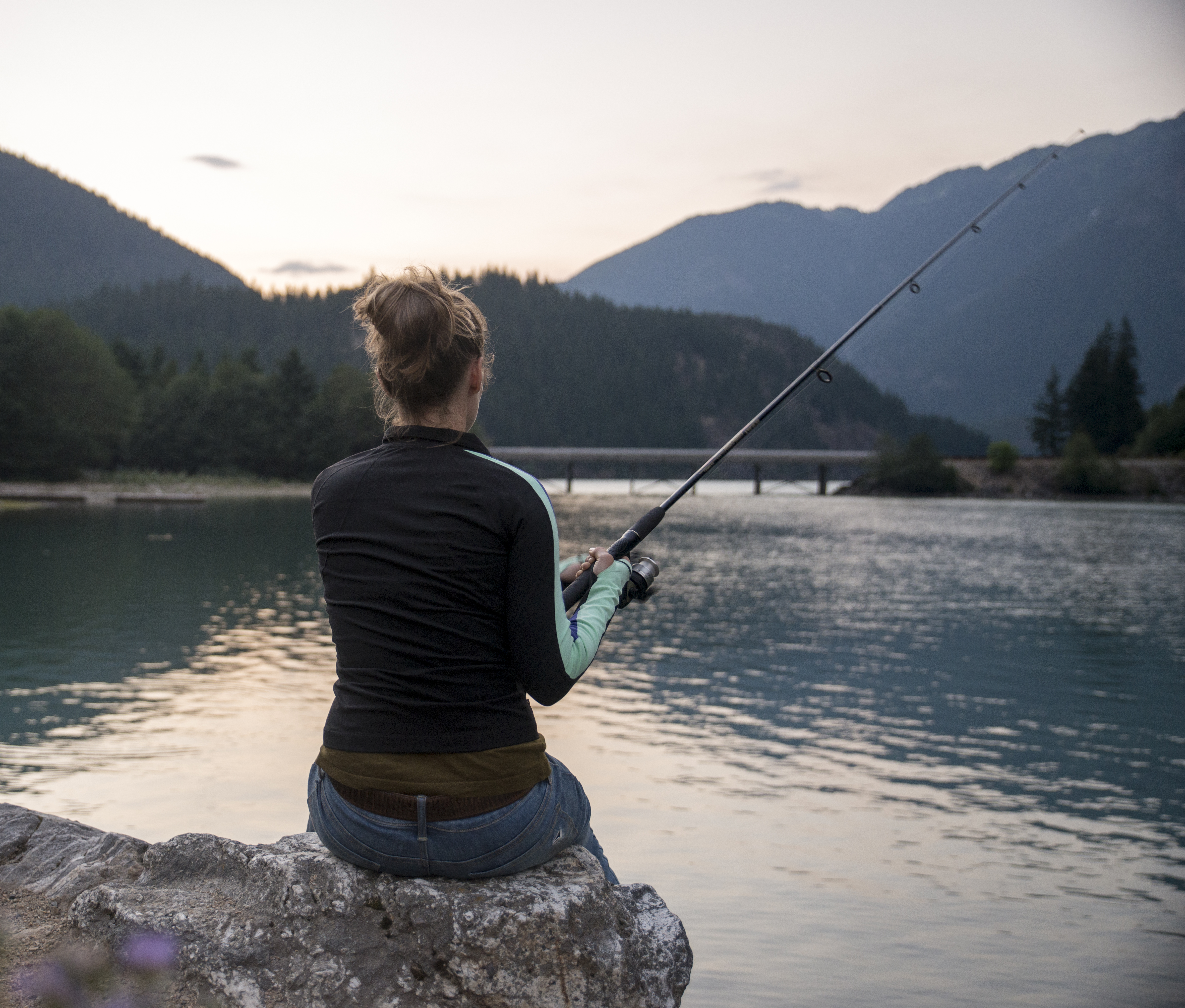 Woman sitting on a rock and fishing.