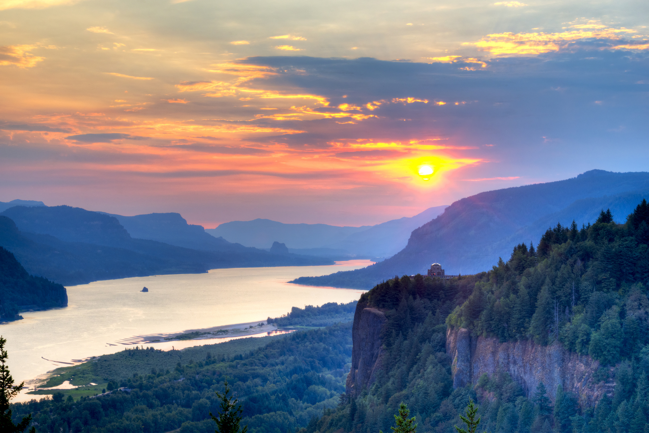 Sunset over a river lined with sheer rock cliffs and lush forests.